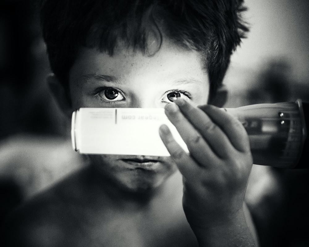 grayscale photo of boy holding light bulb