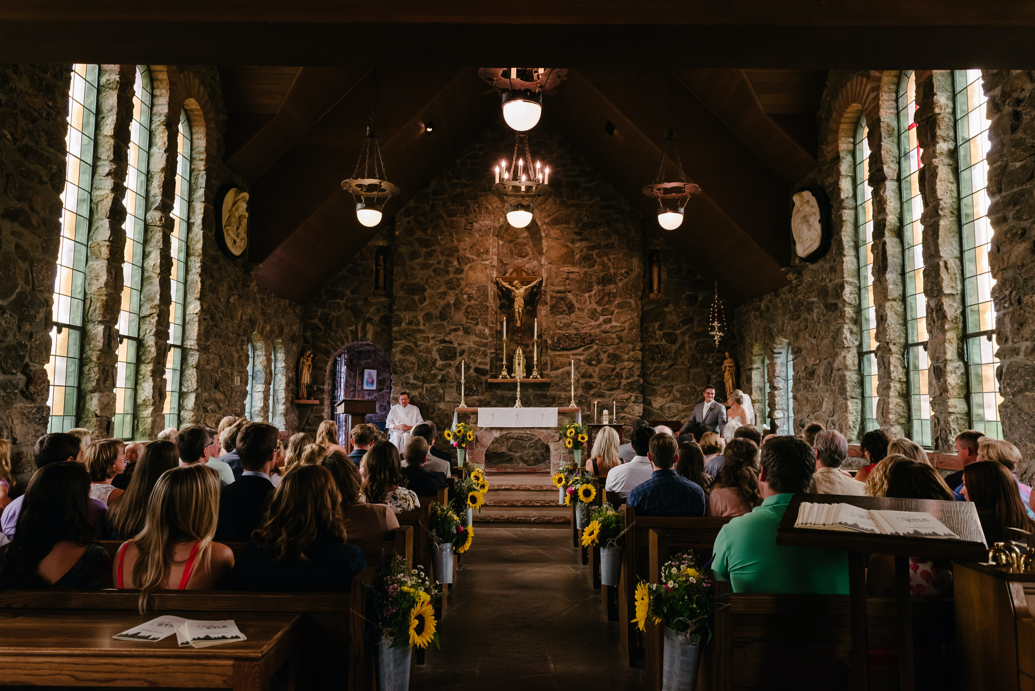 Looking up the aisle of a church wedding with guests sitting in the chapel