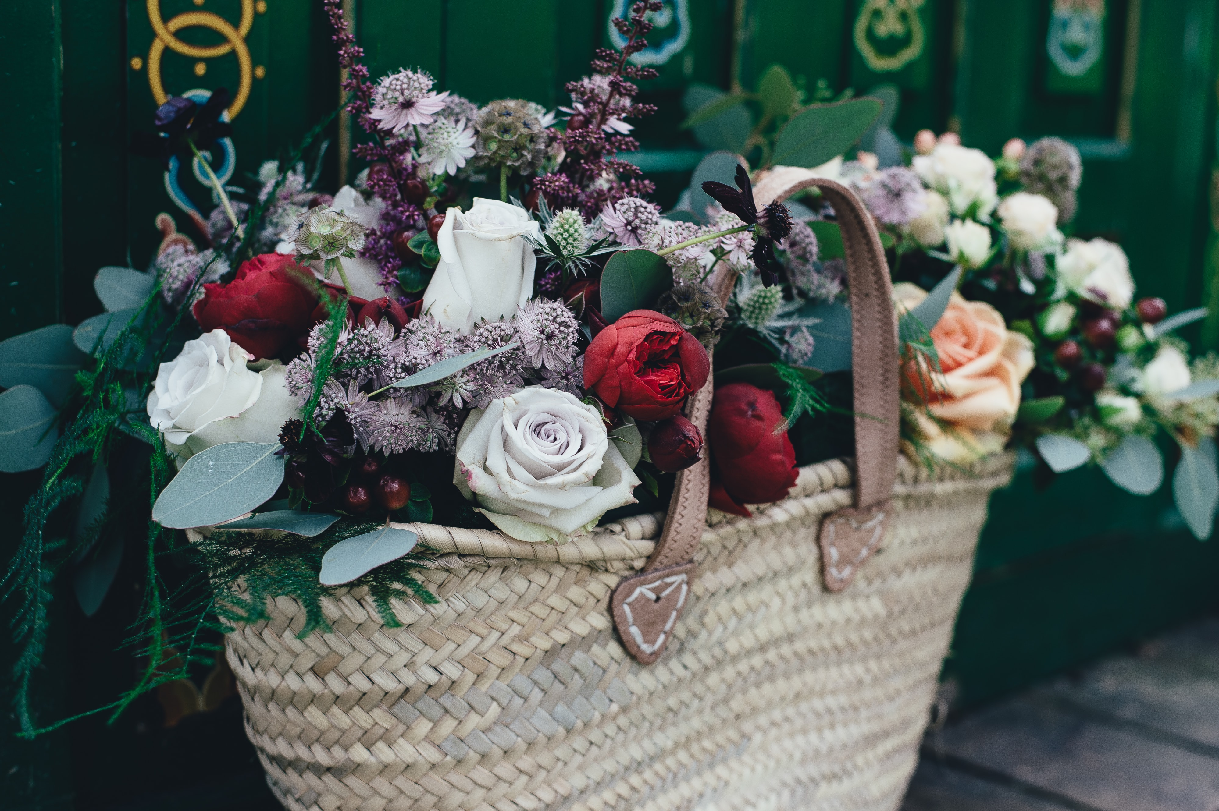 white and red flowers on wicker bag