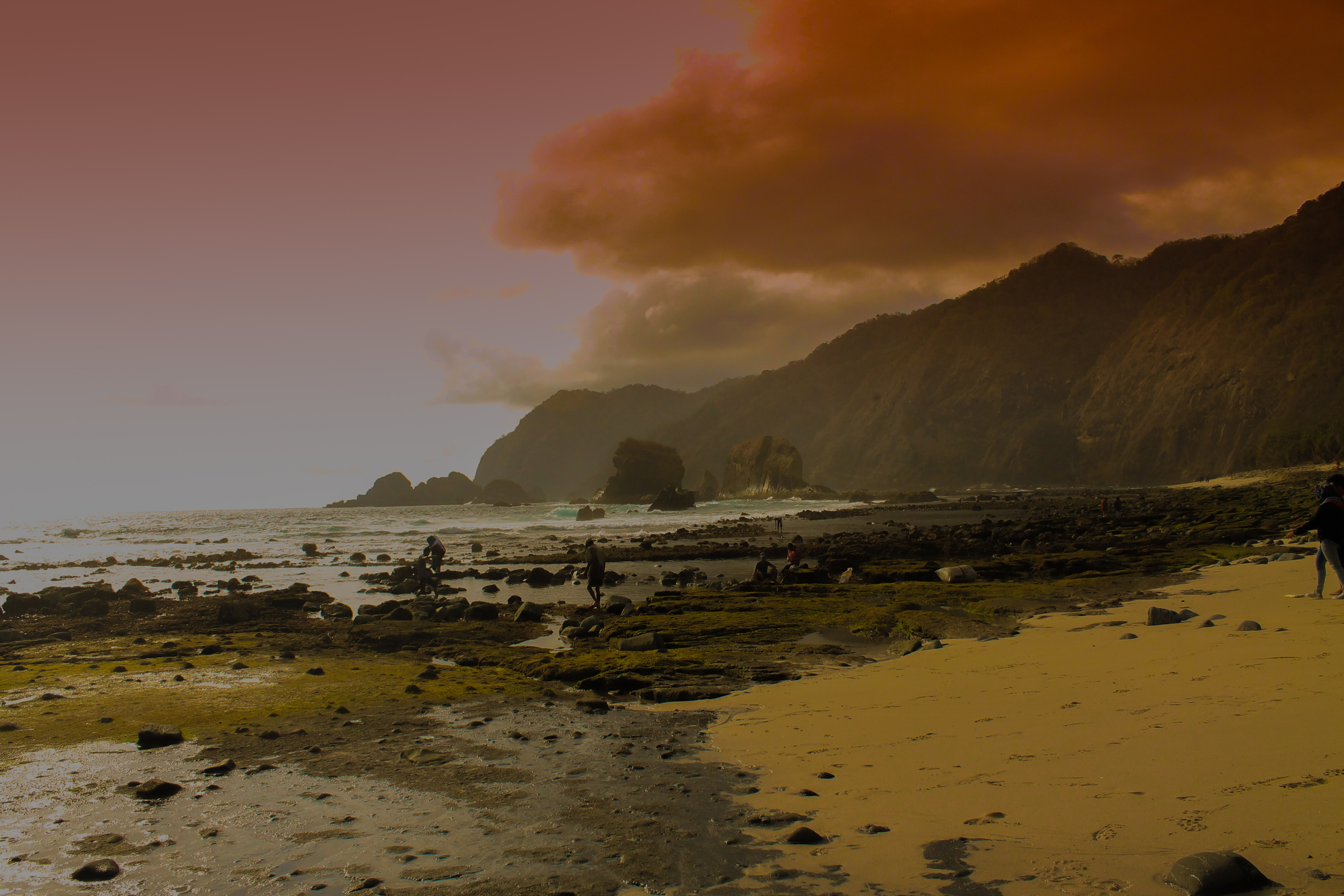 People on the rugged Papuma beach during low tide in Jember