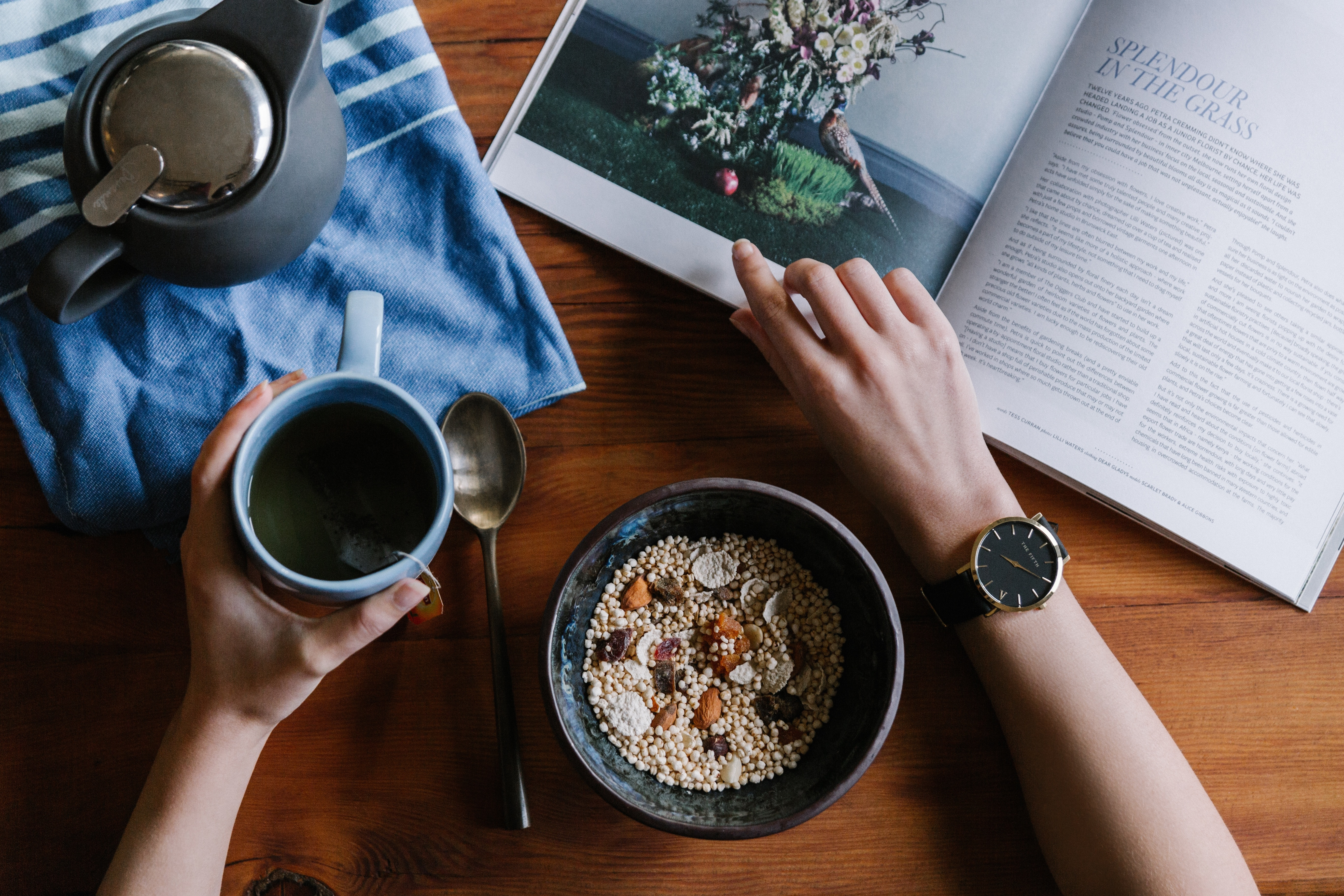 A person reading a book over a cup of coffee and a bowl of granola