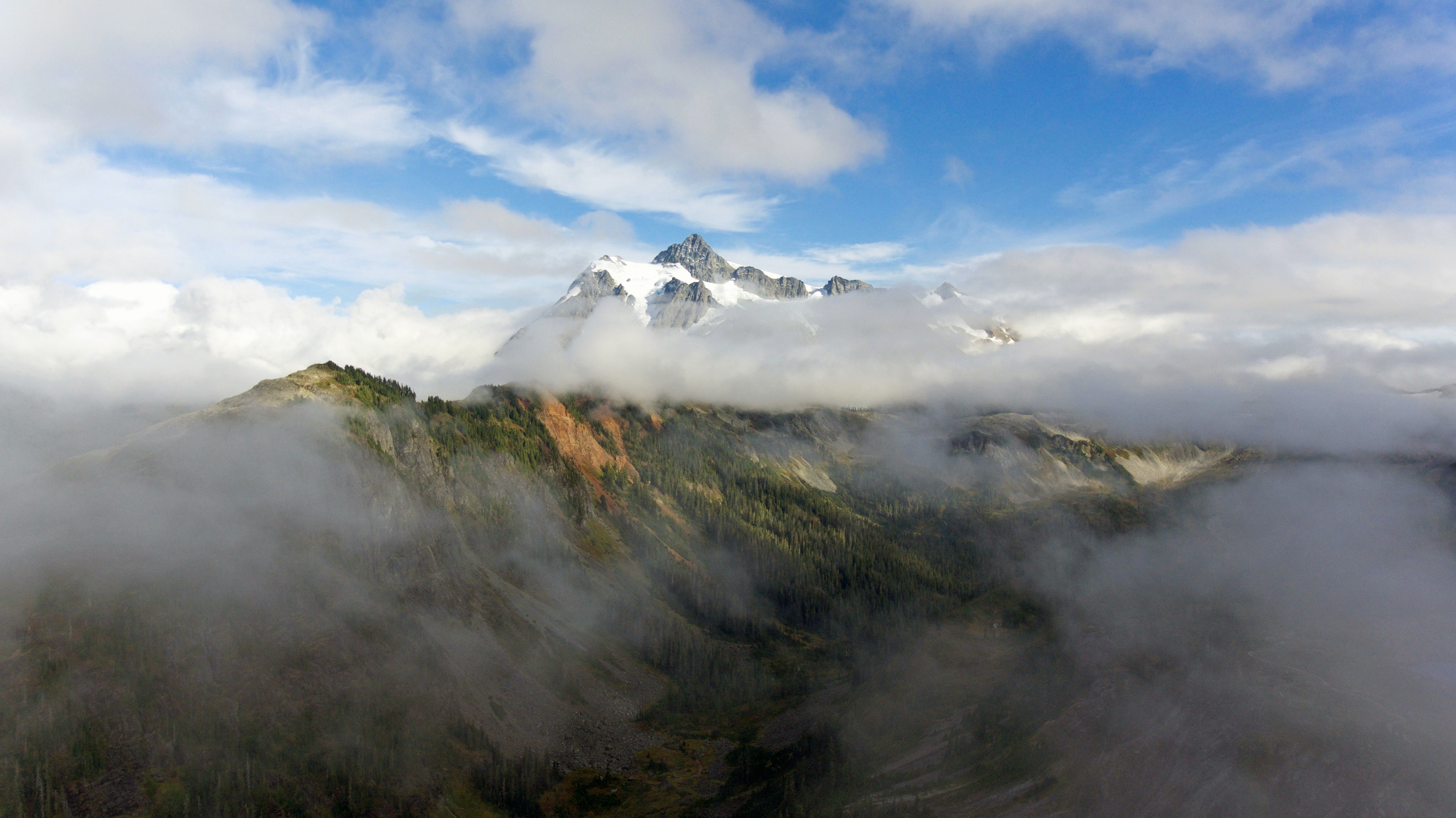 Clouds enveloping snowy peaks towering over forested valleys in the Mount Baker National Forest