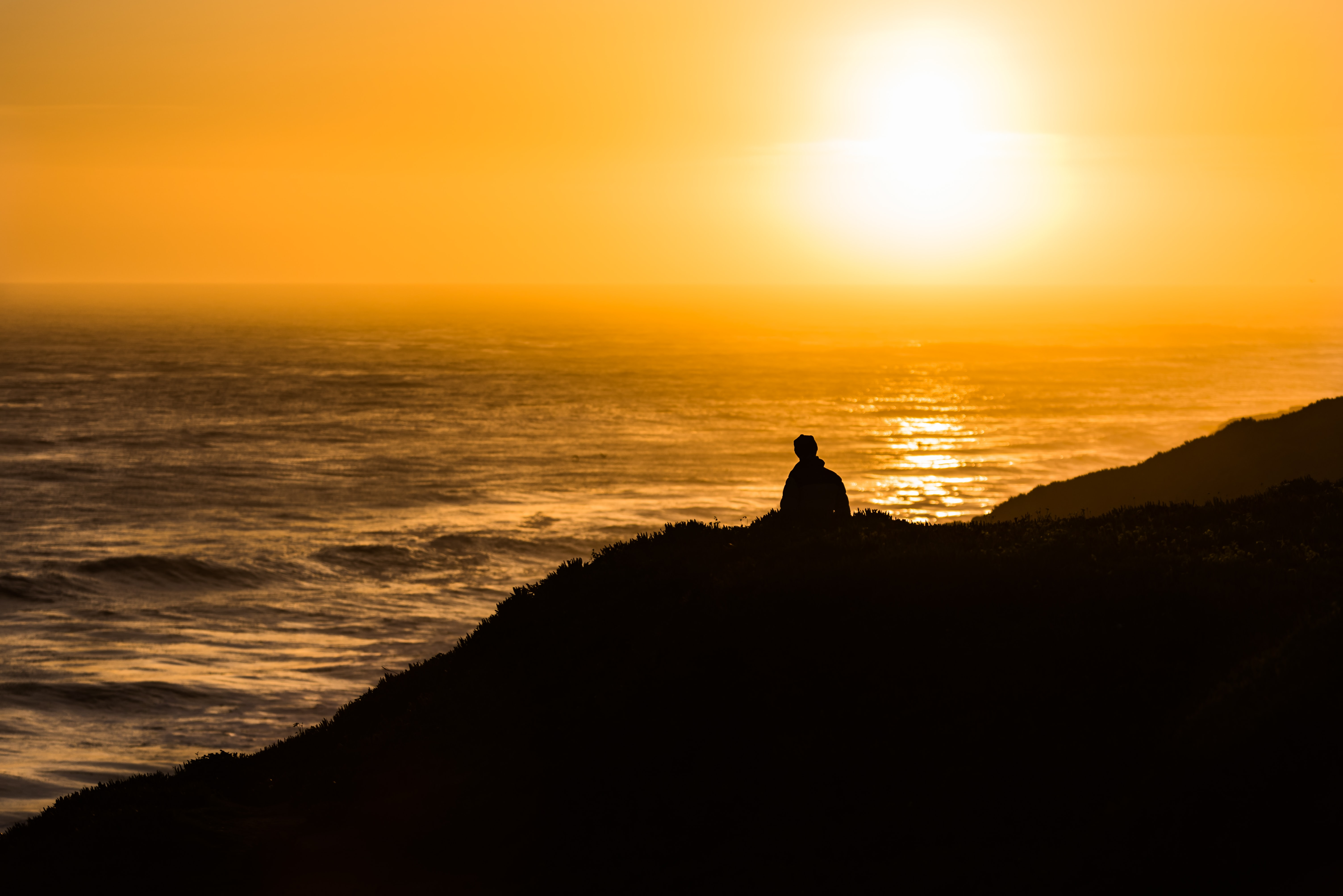 A lonely person sits atop a hill above the ocean of Santa Cruz, watching the orange sunset