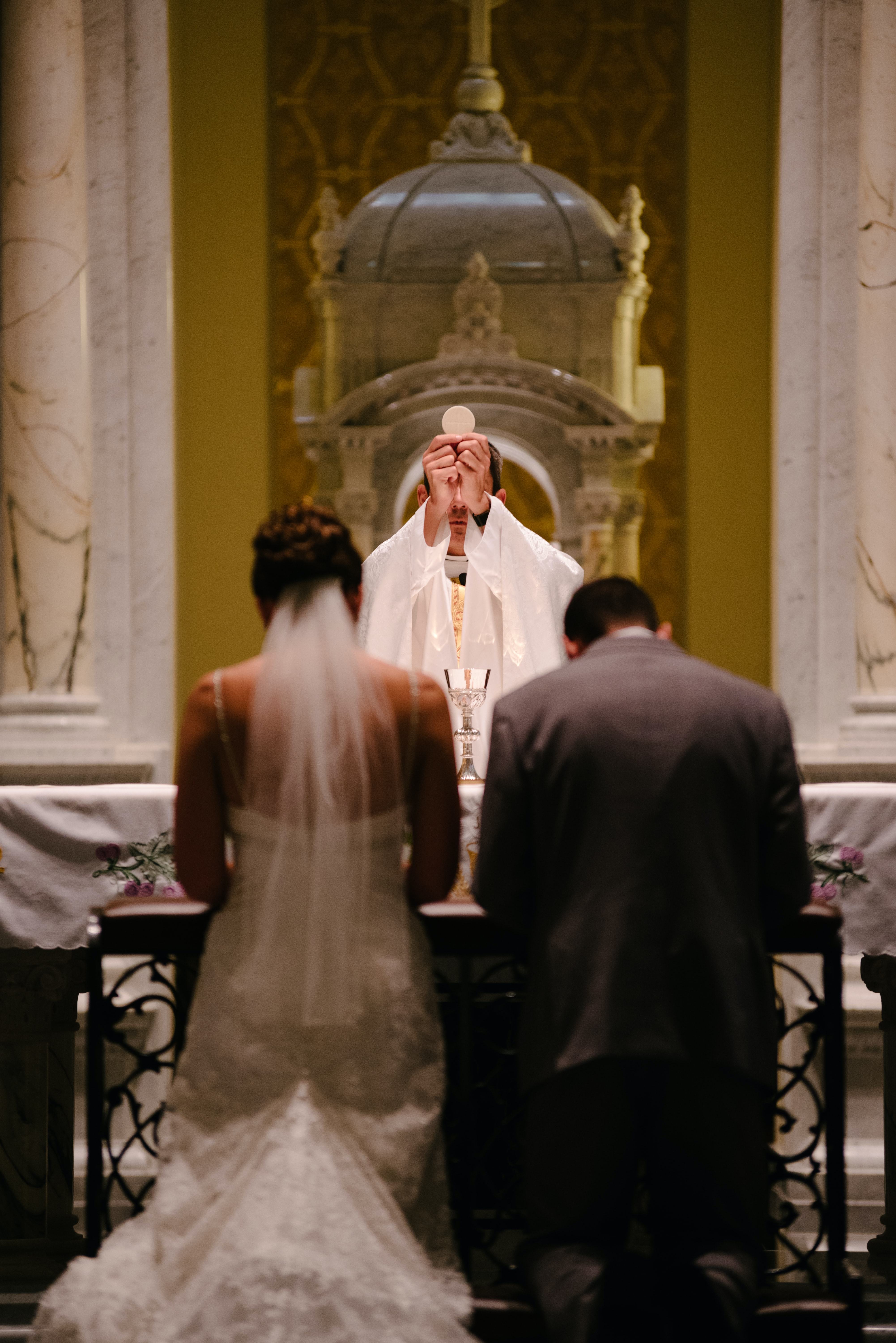 A priest holds up a communion wafer to a couple at the altar at a wedding