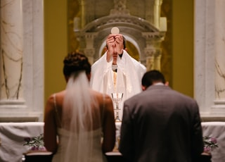 groom and bride kneeling in front of priest raising The Holy Sacrament