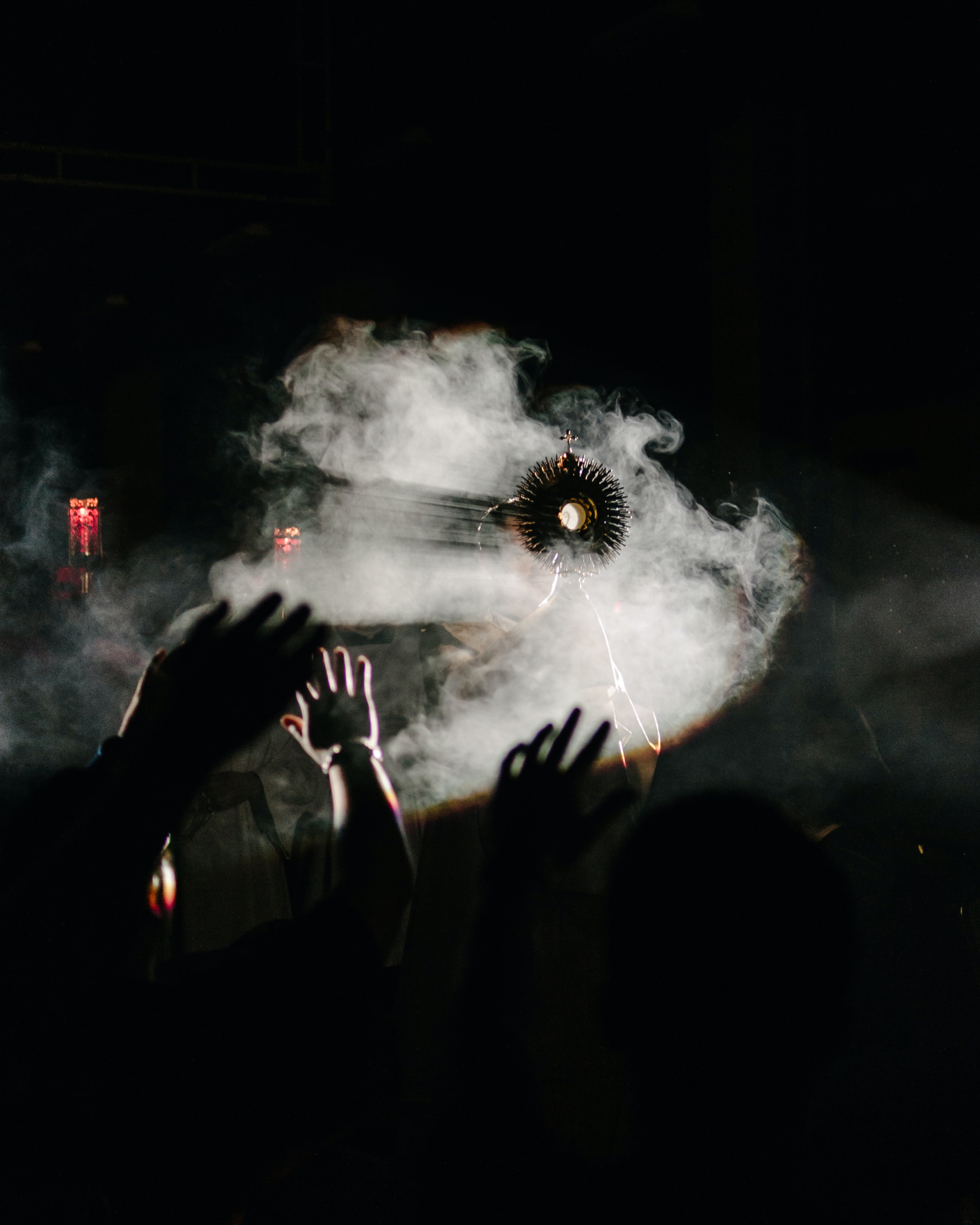 A religious object held up in front of a fog machine, with a crowd raising their hands.