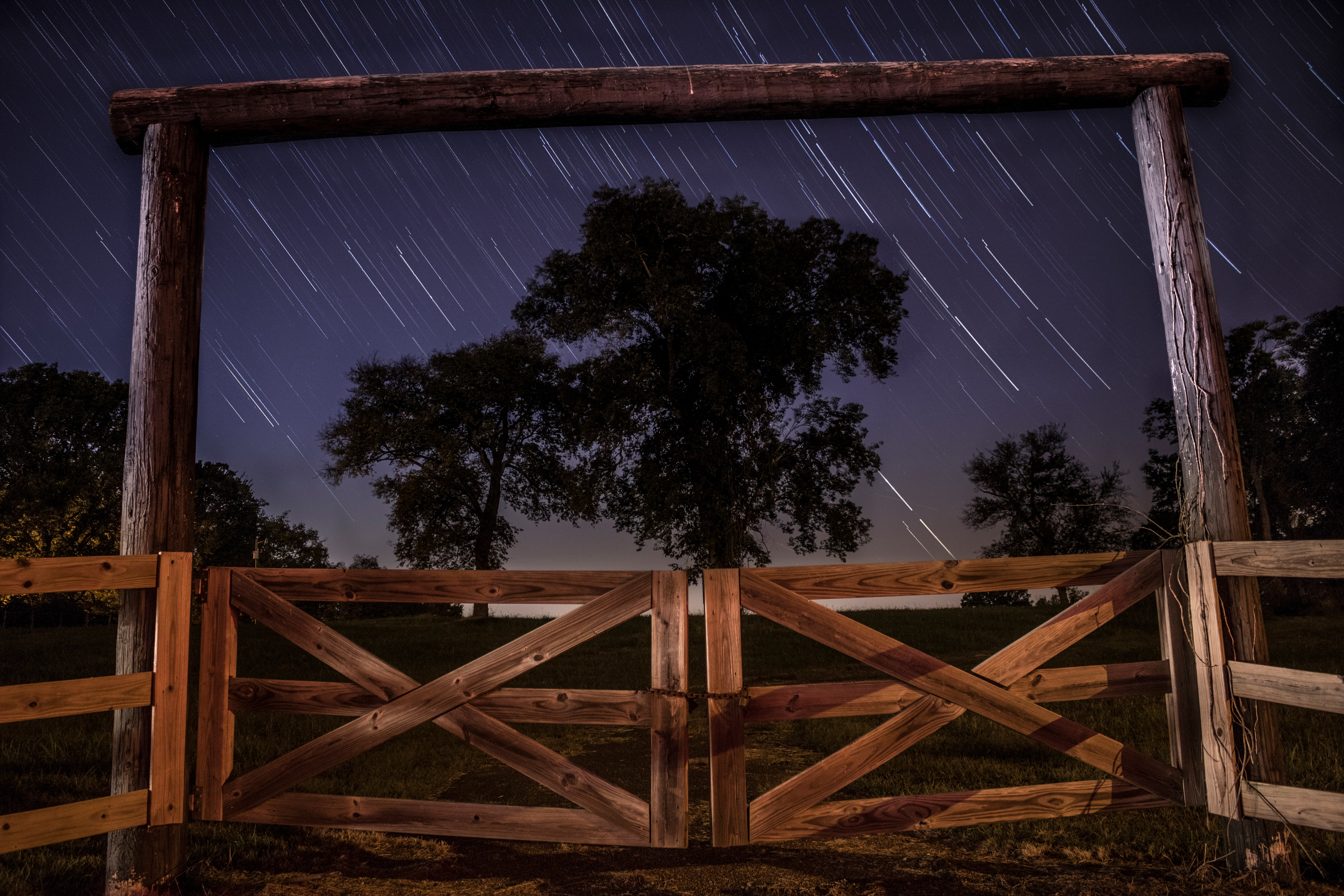 An archway with a gated fence in Lebanon, featuring blurry star trails in the background