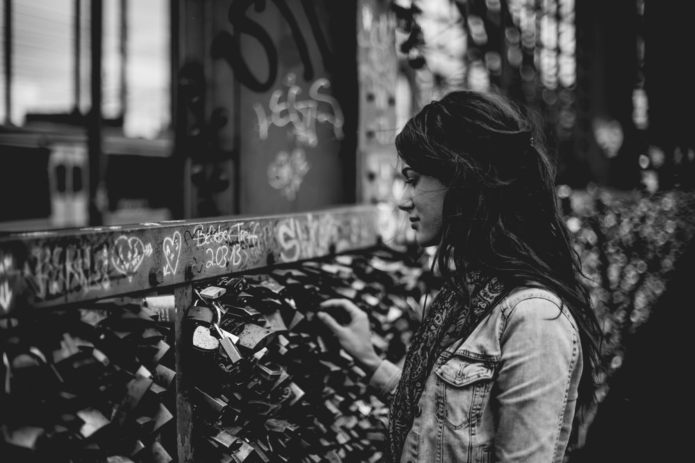 woman holding padlock on bridge