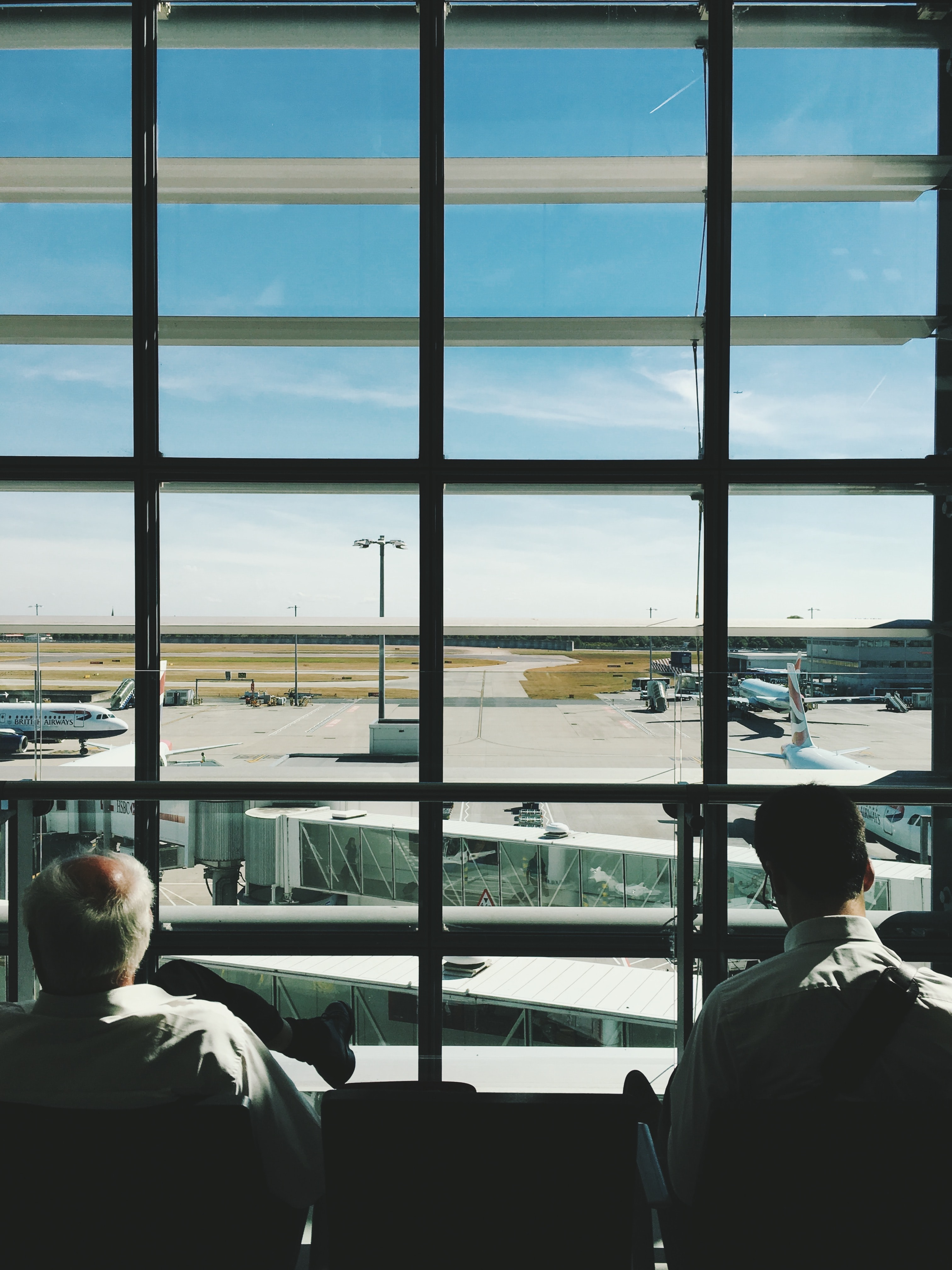 Sitting at an airport looking out at the runway from the terminal windows at Heathrow Airport.