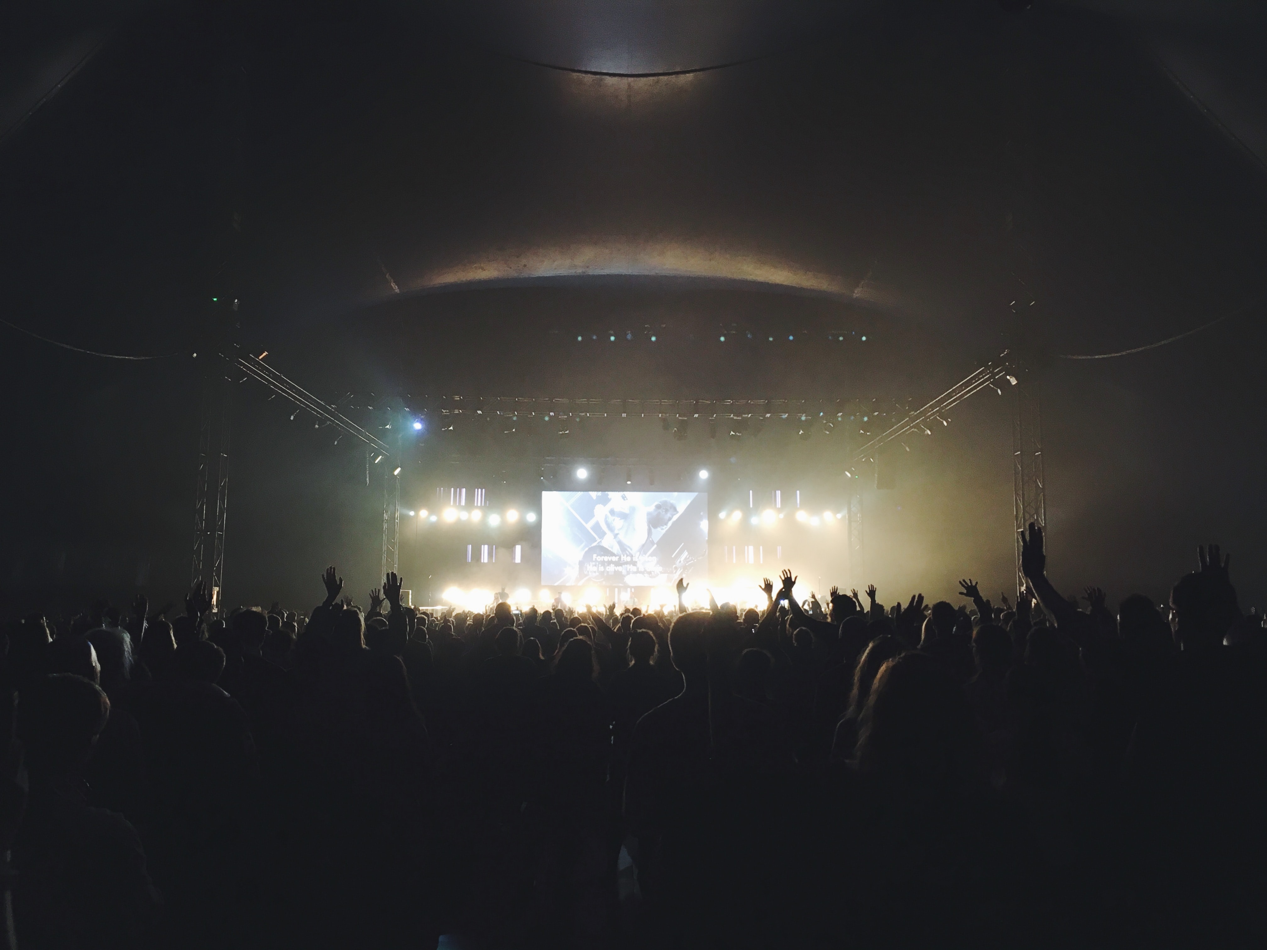 A shot from the back of a large concert audience with a large screen above the performing band