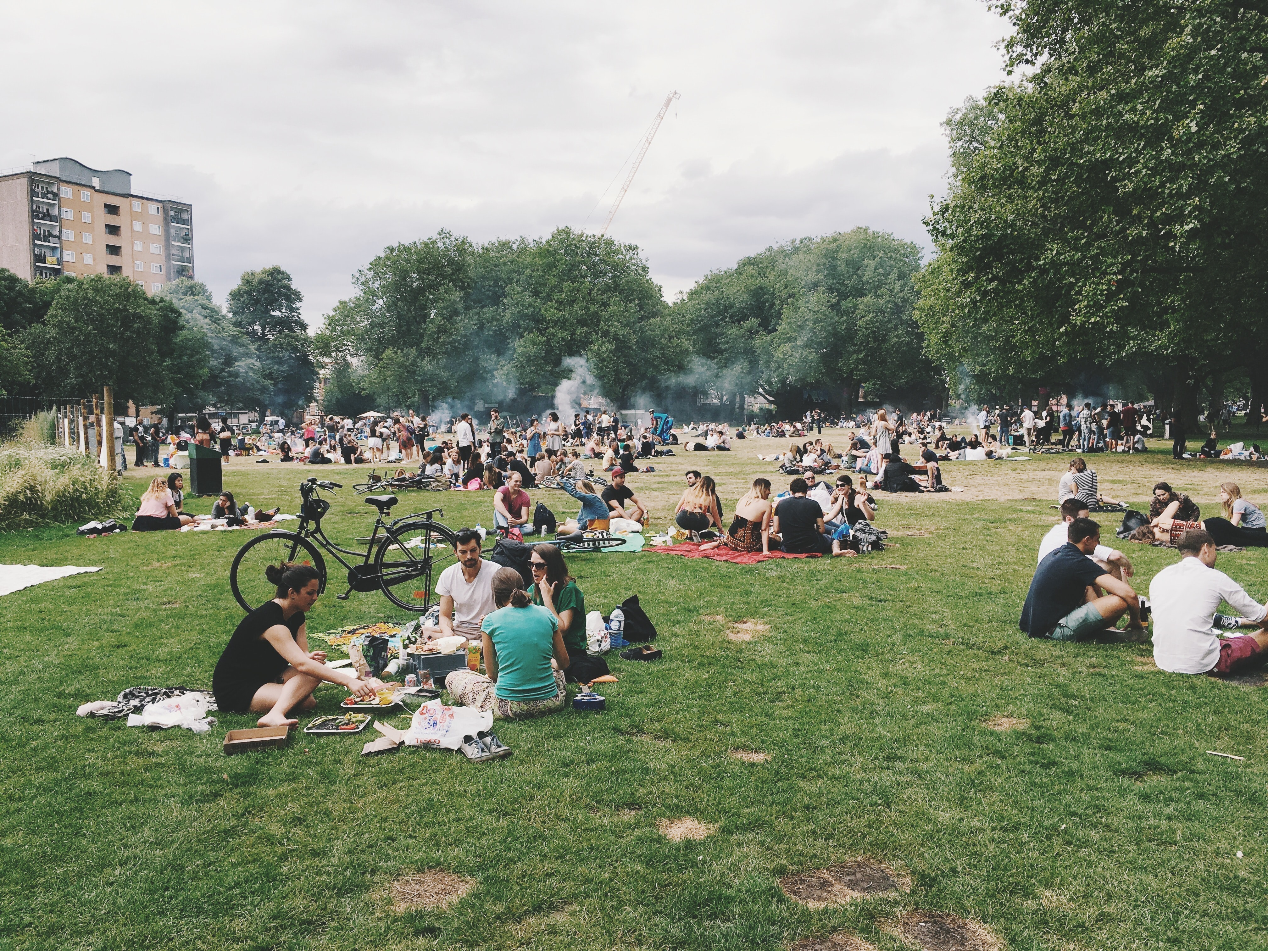 Diverse crowd of people sit and picnic in an urban park
