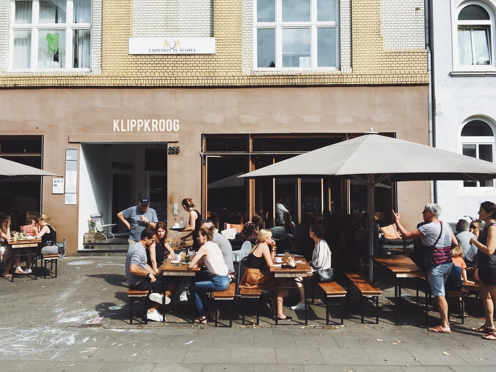 group of people sitting on benches with tables beside Klippkroog store front at daytime
