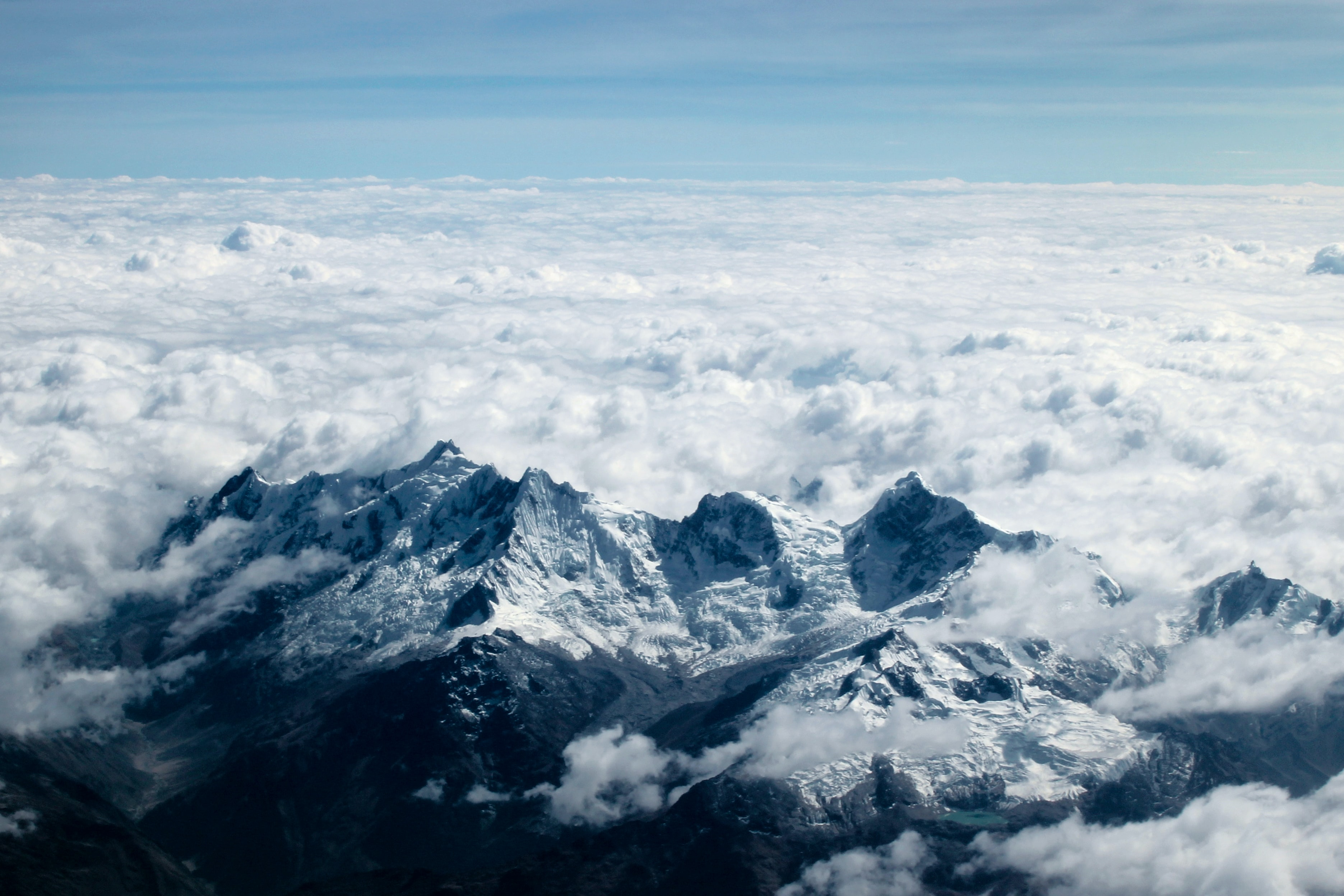 A snowy mountain ridge with thick clouds stretching over the land to the horizon