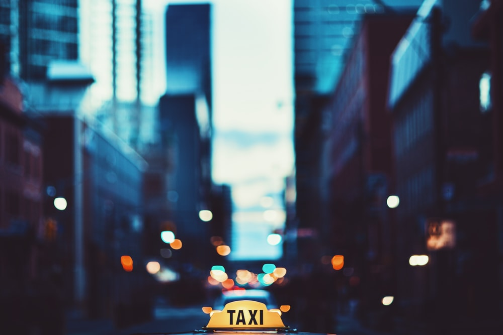 selective focus photography of taxi signage