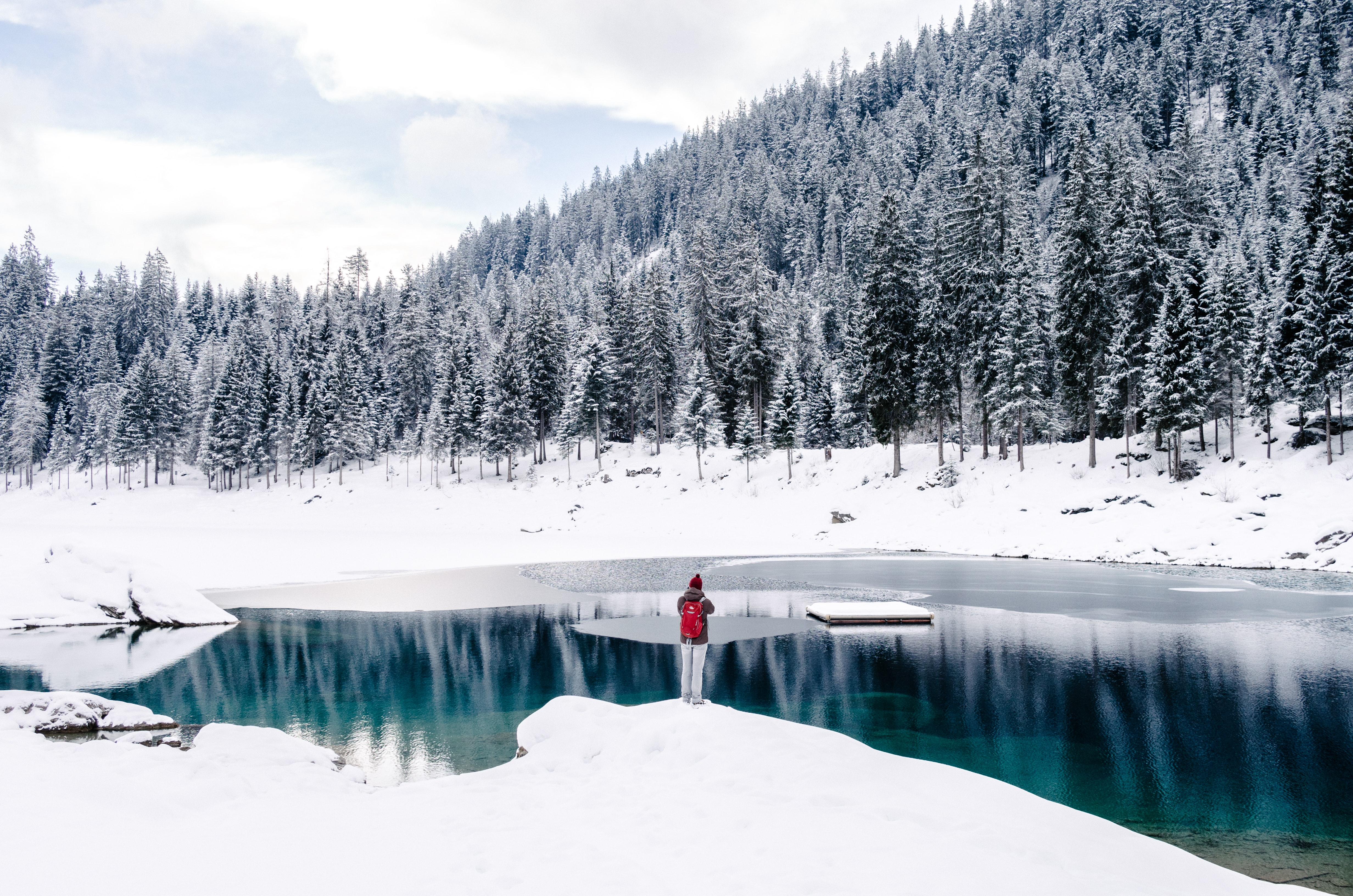 A person standing in front of a mountain pond at the Grisons canton in Switzerland