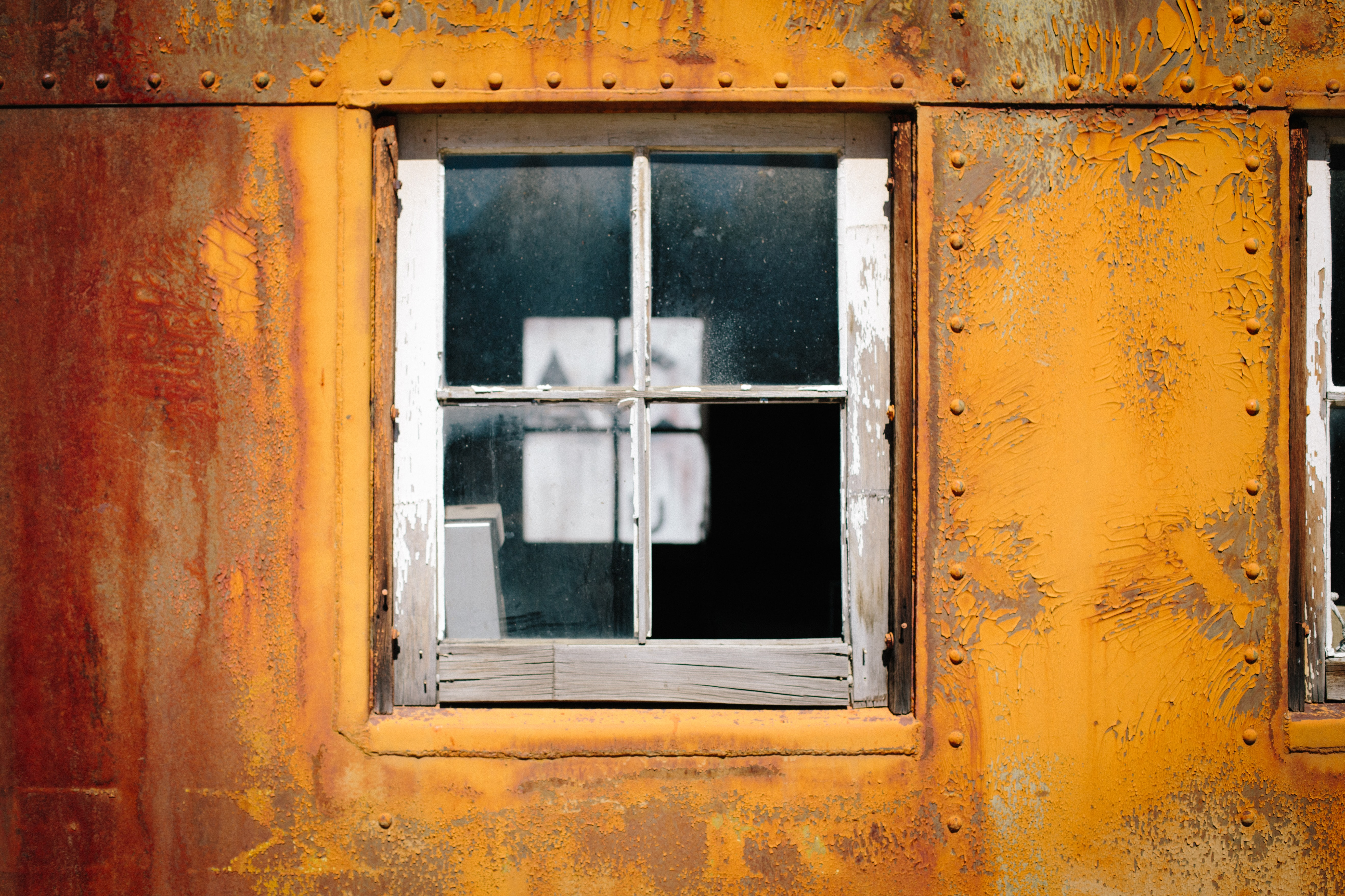 The close-up view of a glass window of a rusty and old metal building in western pacific railroad museum.
