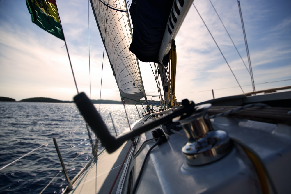 Reel on sailboat with sails sailing on water with horizon in the background