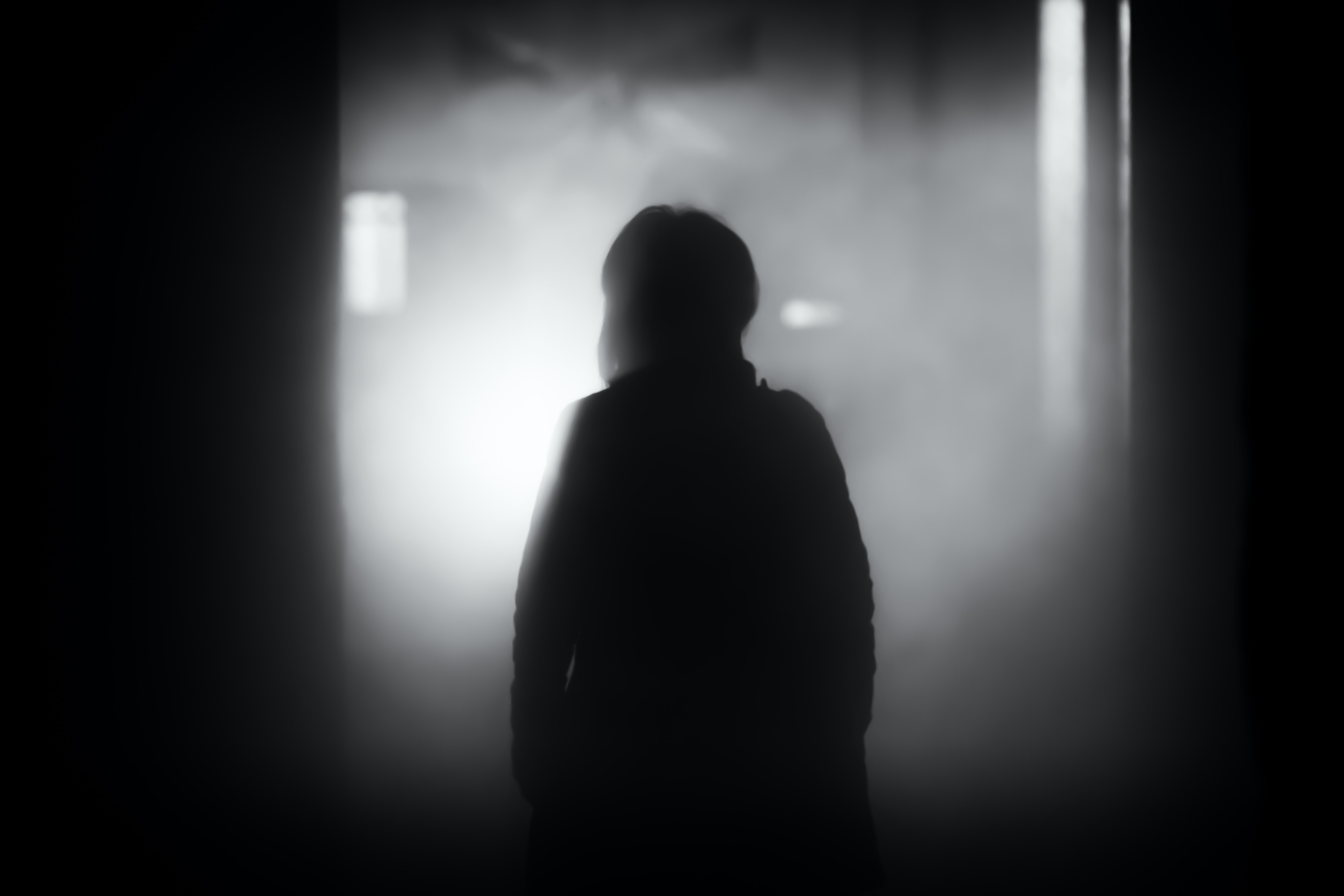 A dark silhouette of a person staring at lights and shadows in a building