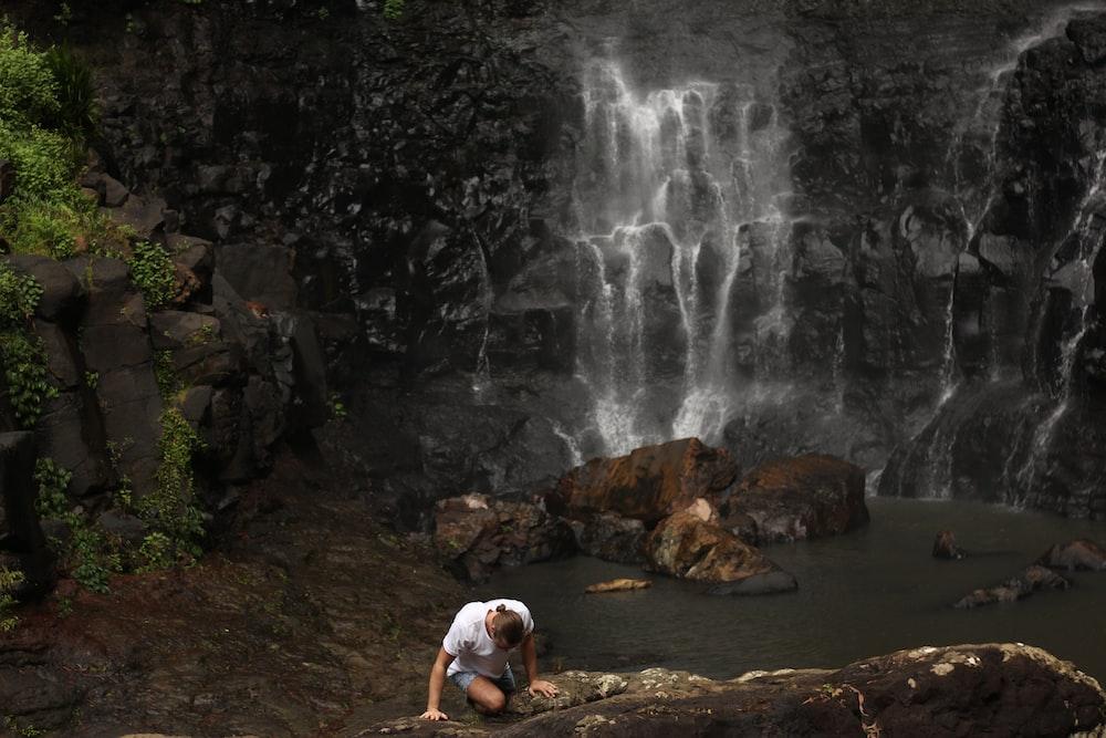 person climbing on rock near water fall