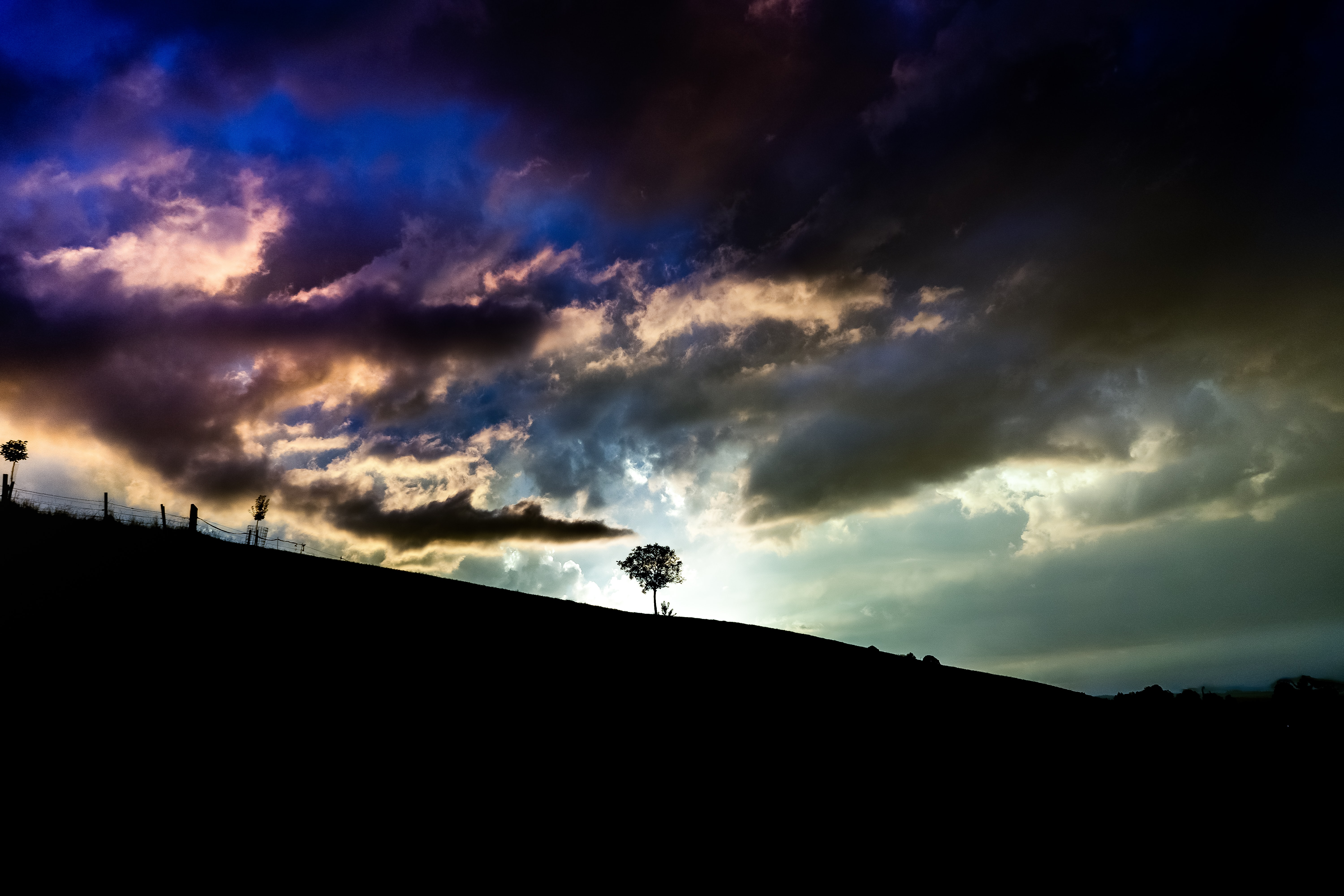 A dark sunset in the horizon casts shadows on a hill where some trees and fences stand in Höfen