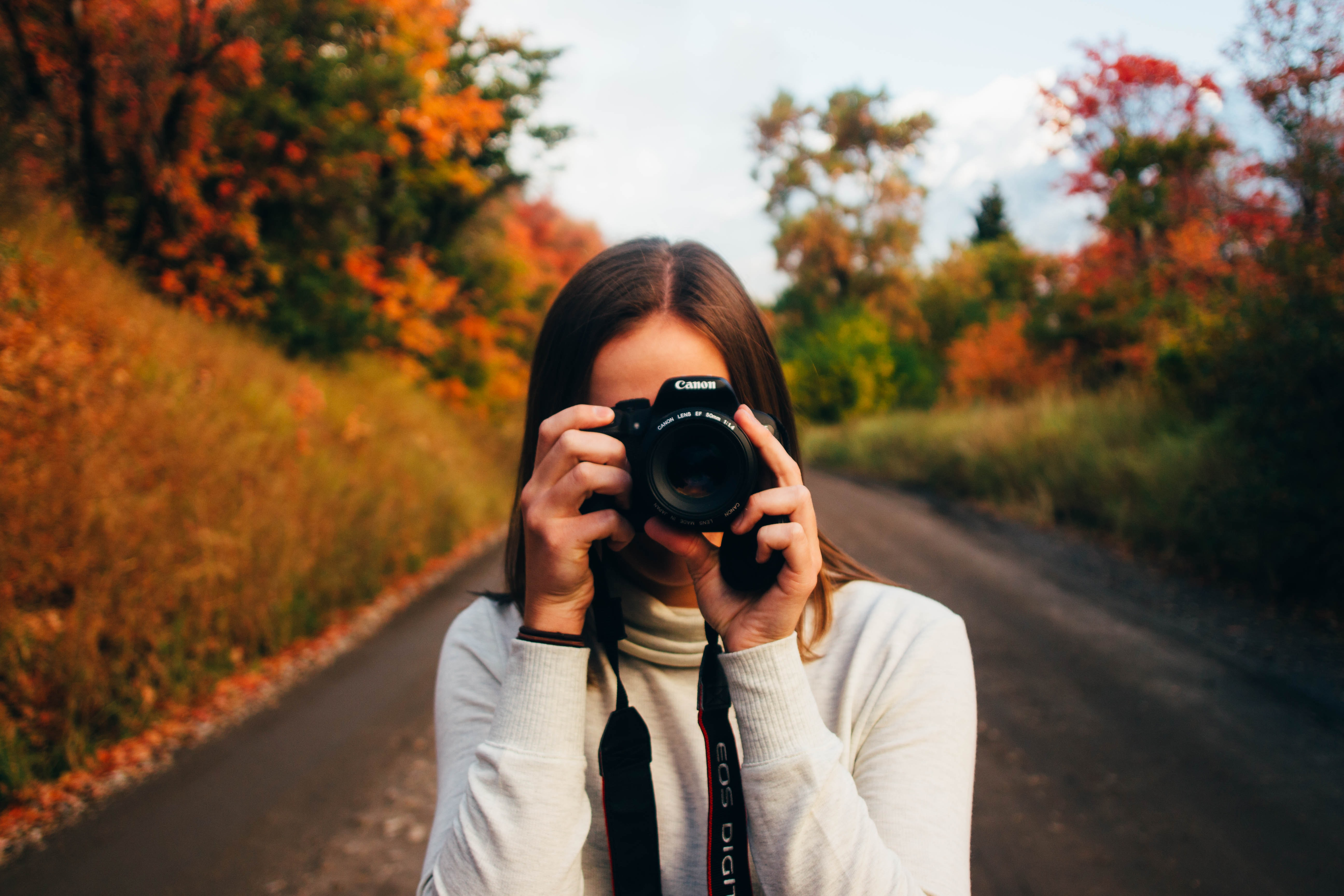 A woman holding a Canon camera with fall foliage behind her