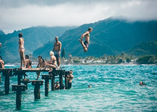 man diving from dock with people