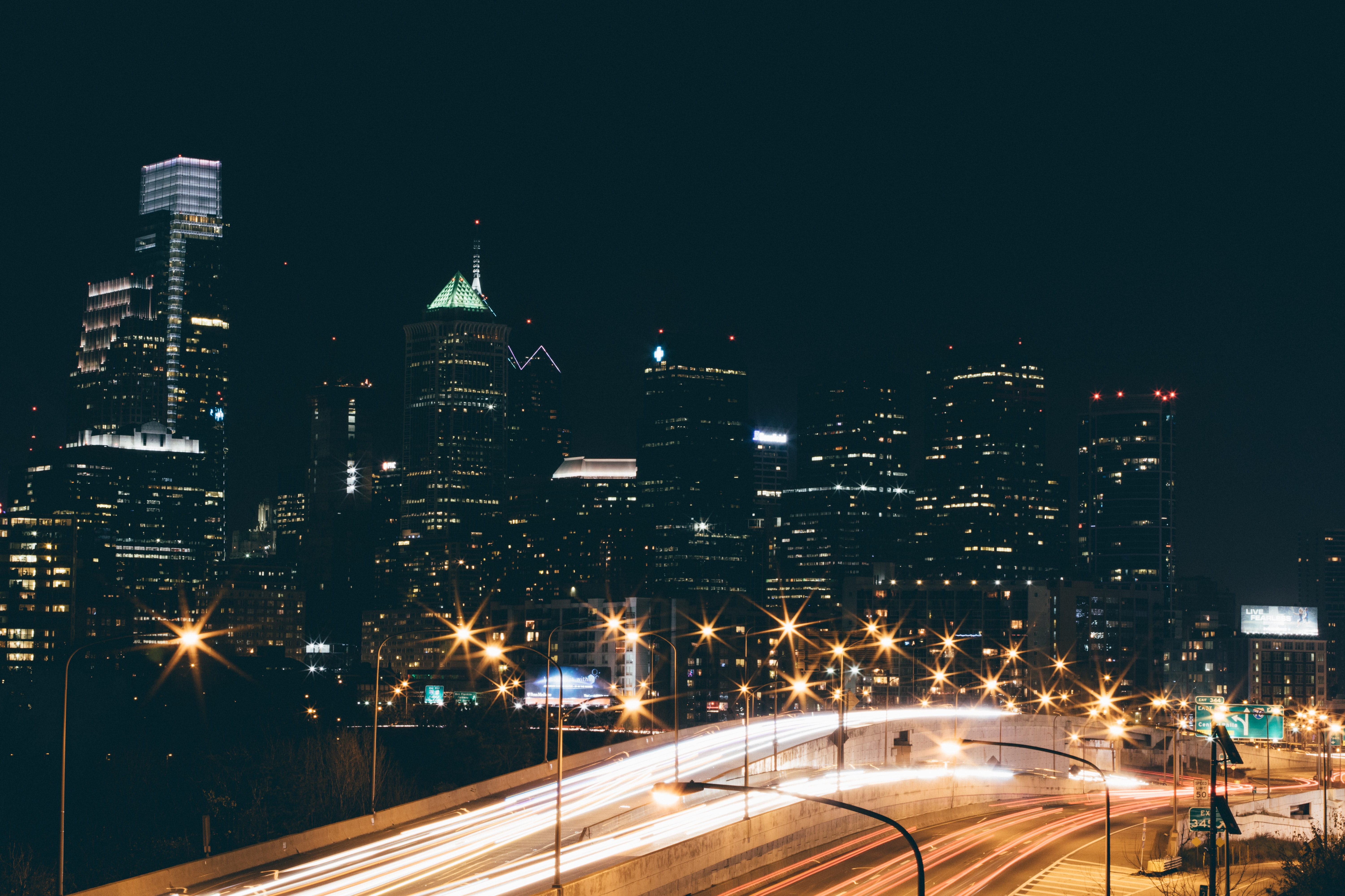 A long-exposure shot of a freeway in Philadelphia with light trails on the road and highrises at the back