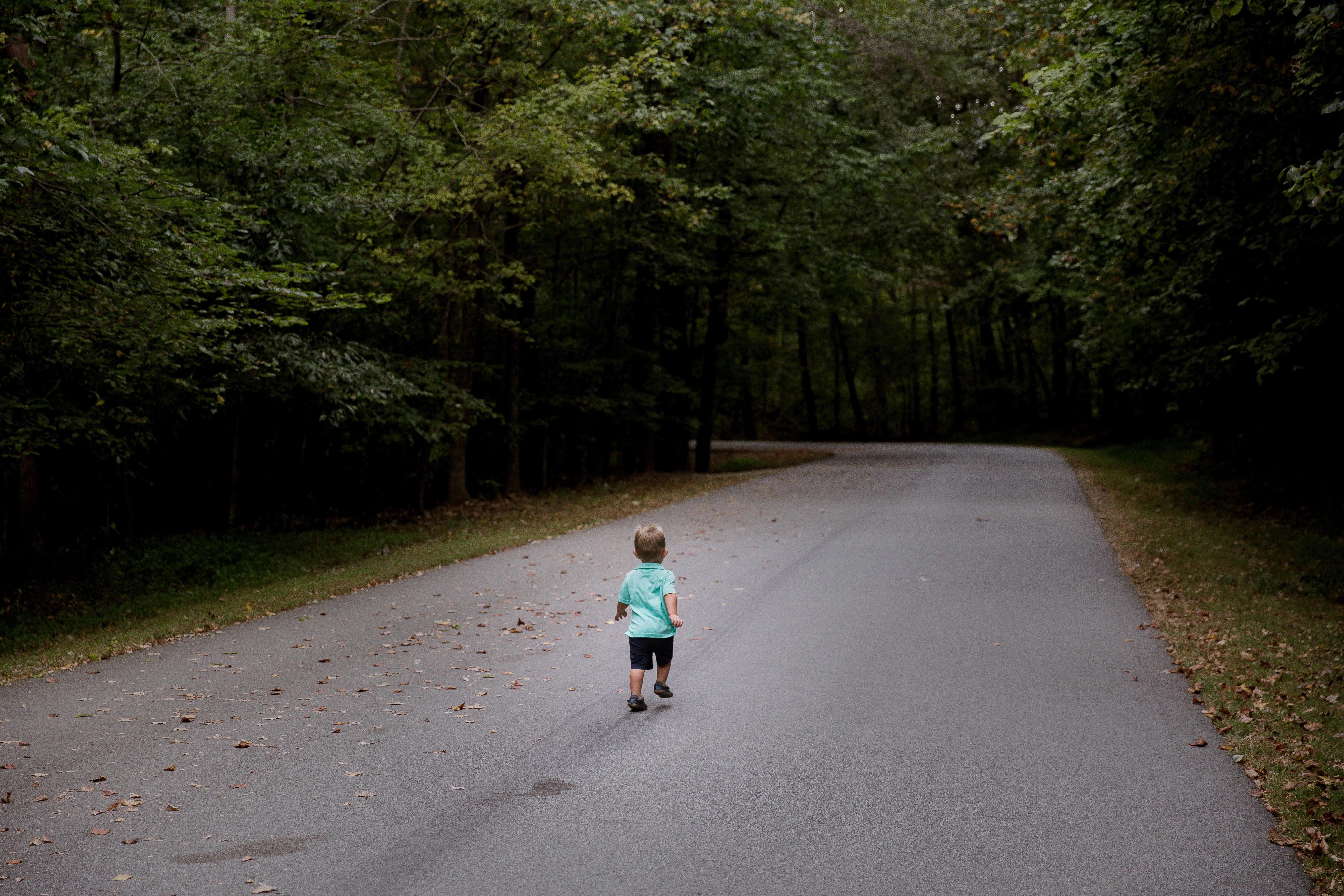 A little boy running down a street by himself