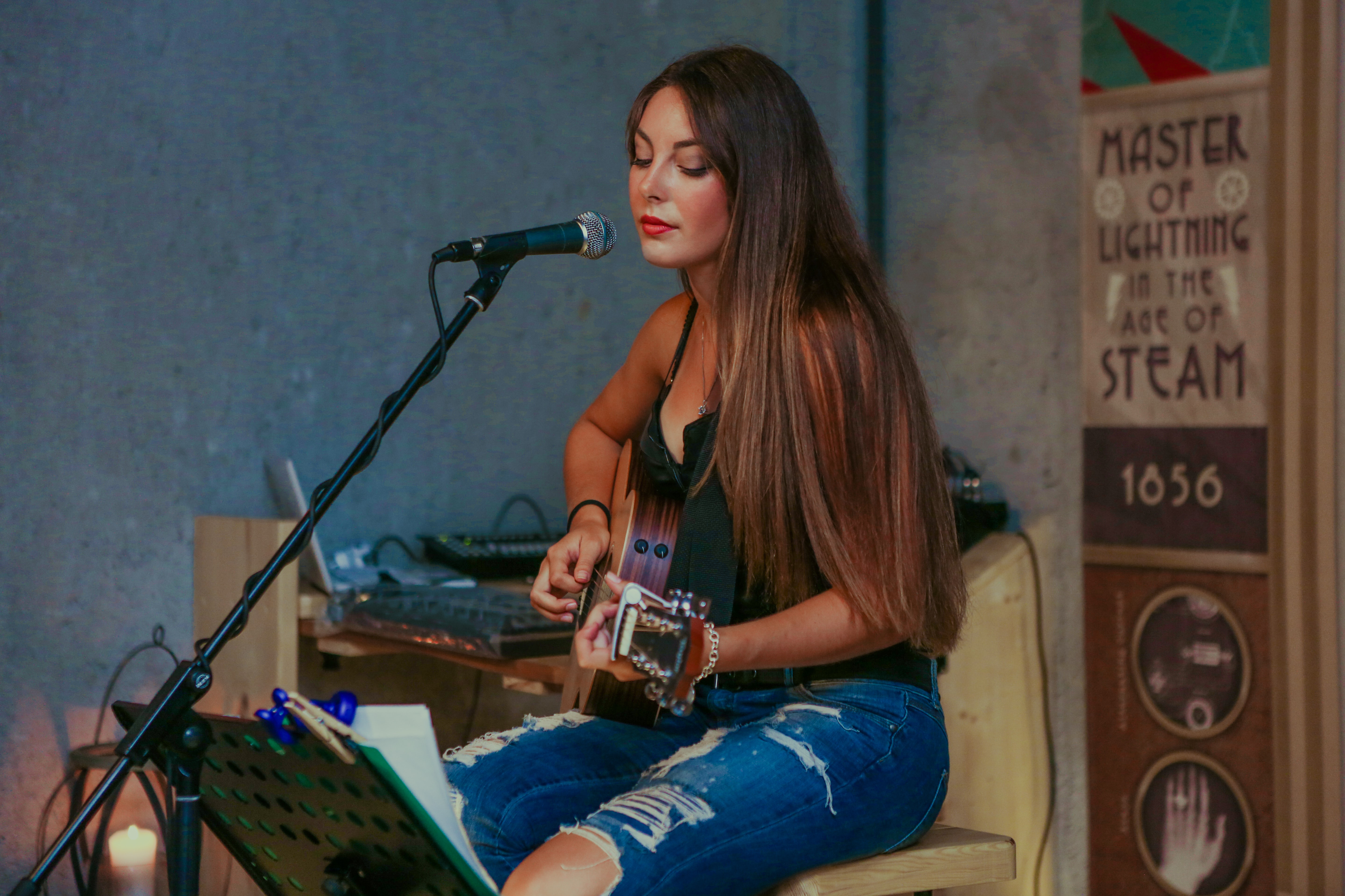 A dark-haired woman in ripped jeans playing acoustic guitar