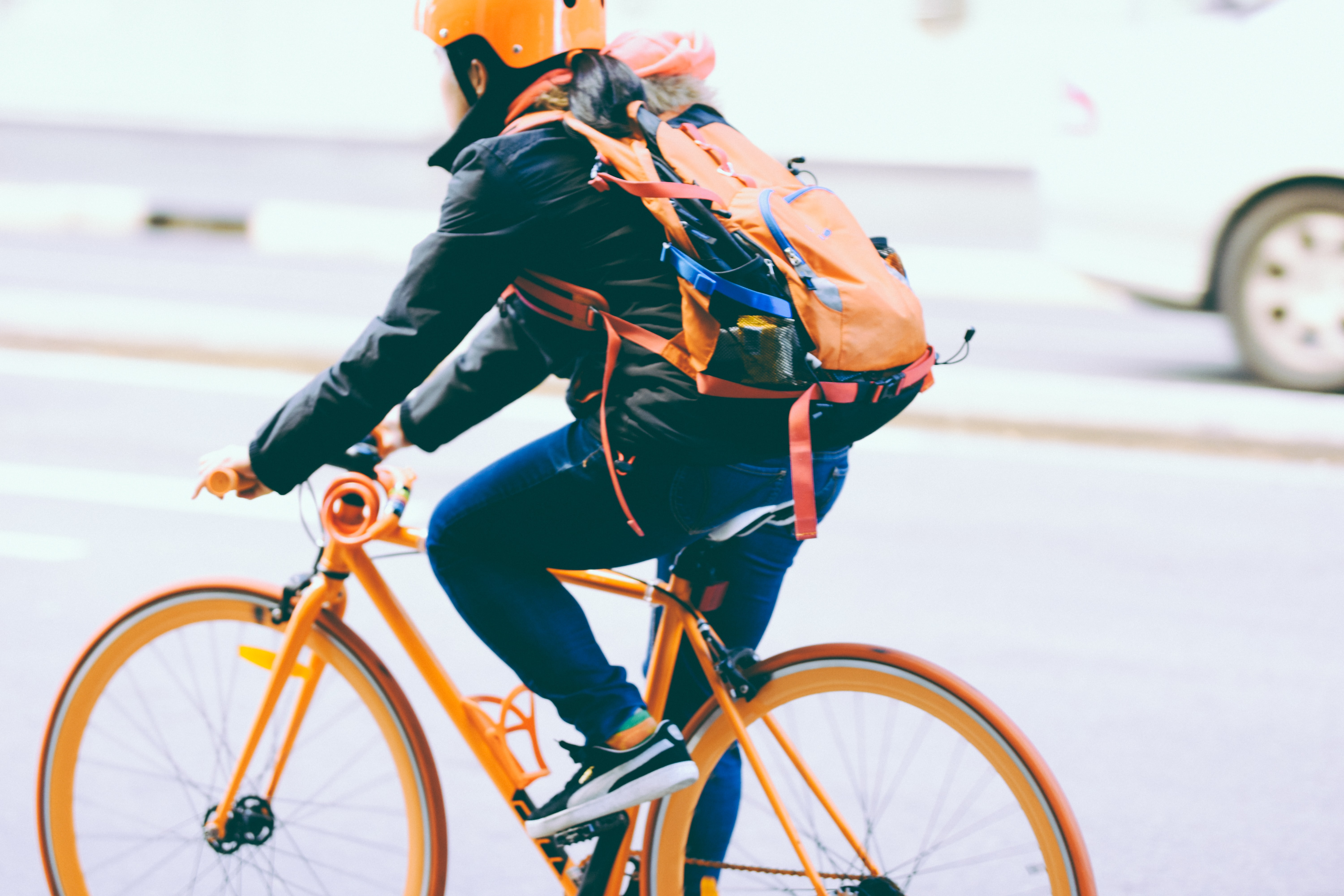 A woman with a backpack riding an orange bicycle