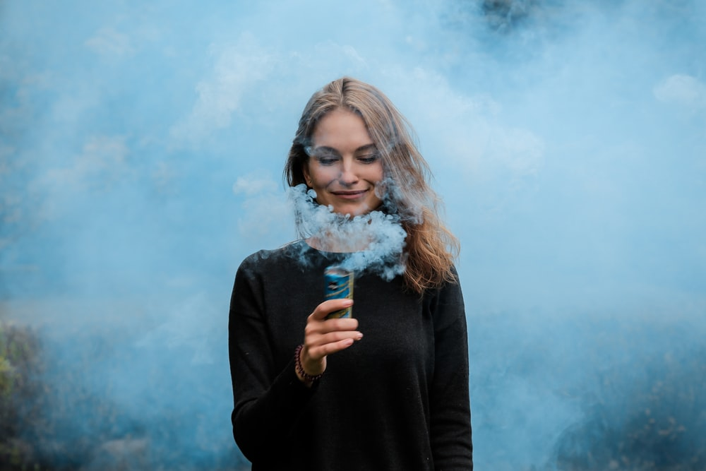 shallow focus photography of woman surrounded by smoke