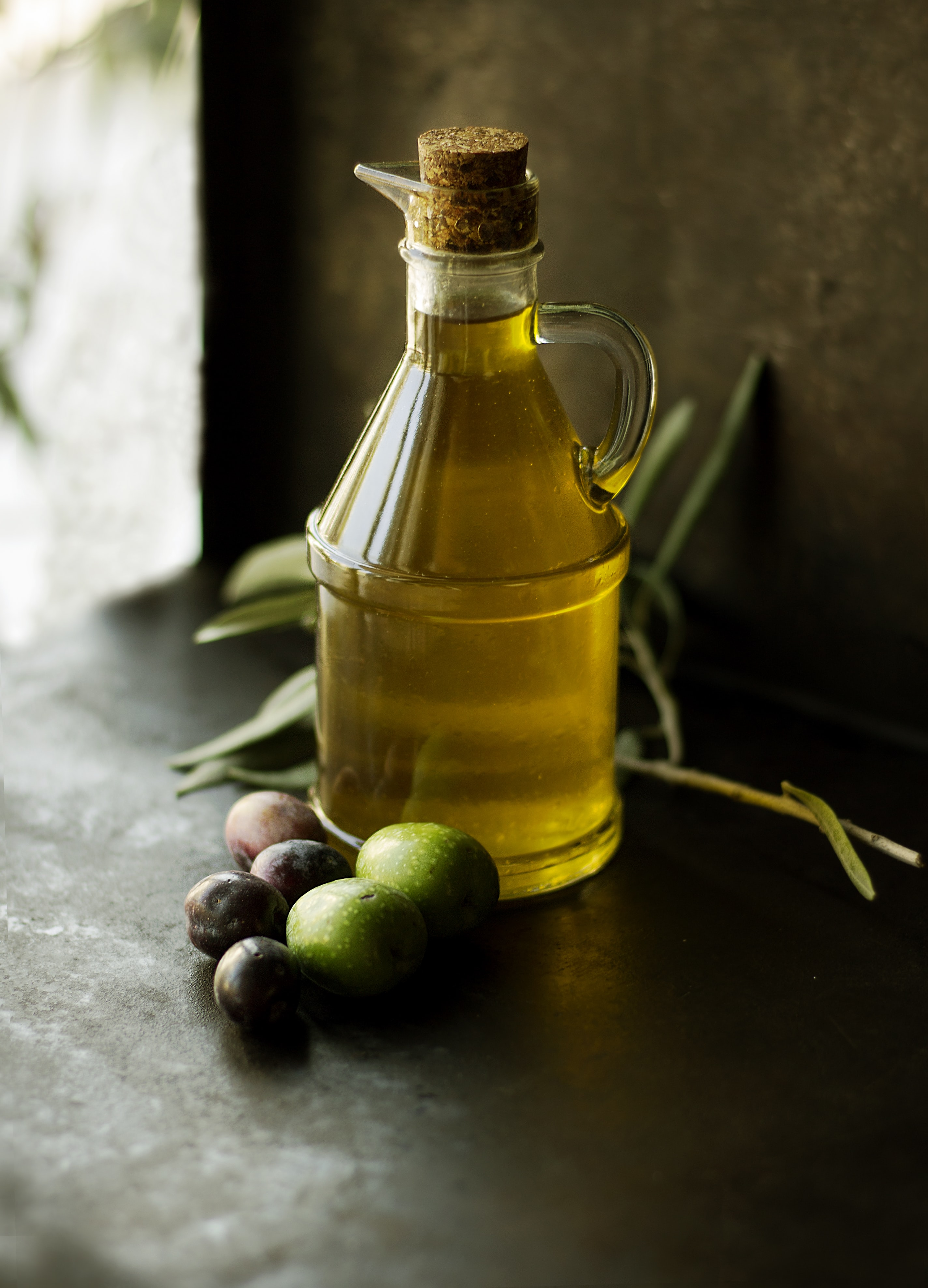A glass jug of extra virgin olive oil next to some fruit on a table