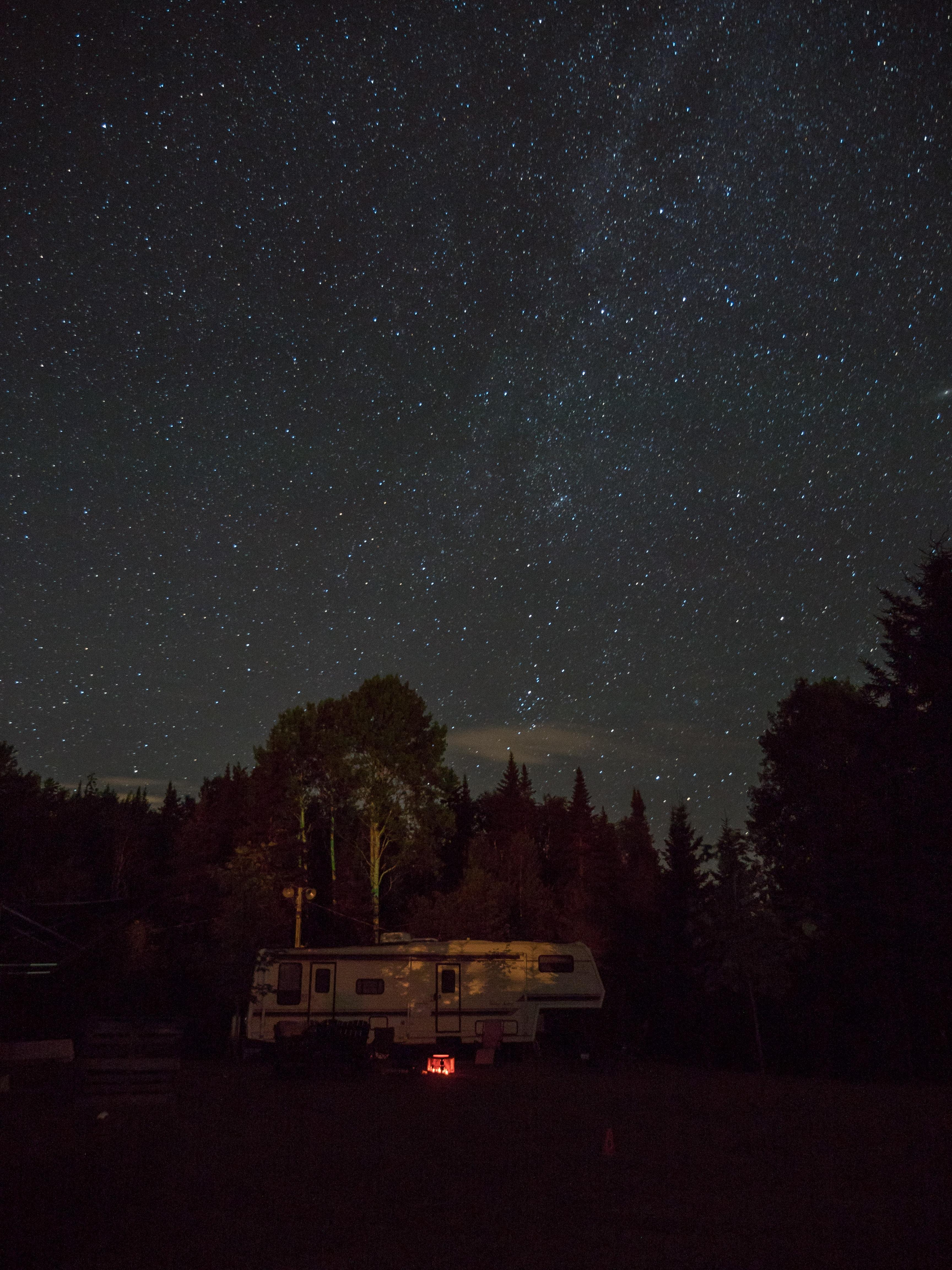 An RV parked near a forest under a starry evening sky