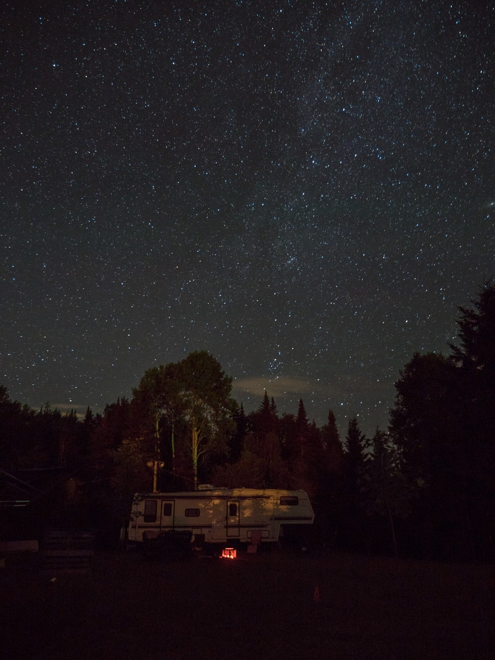 white RV trailer surrounded by trees during nighttime
