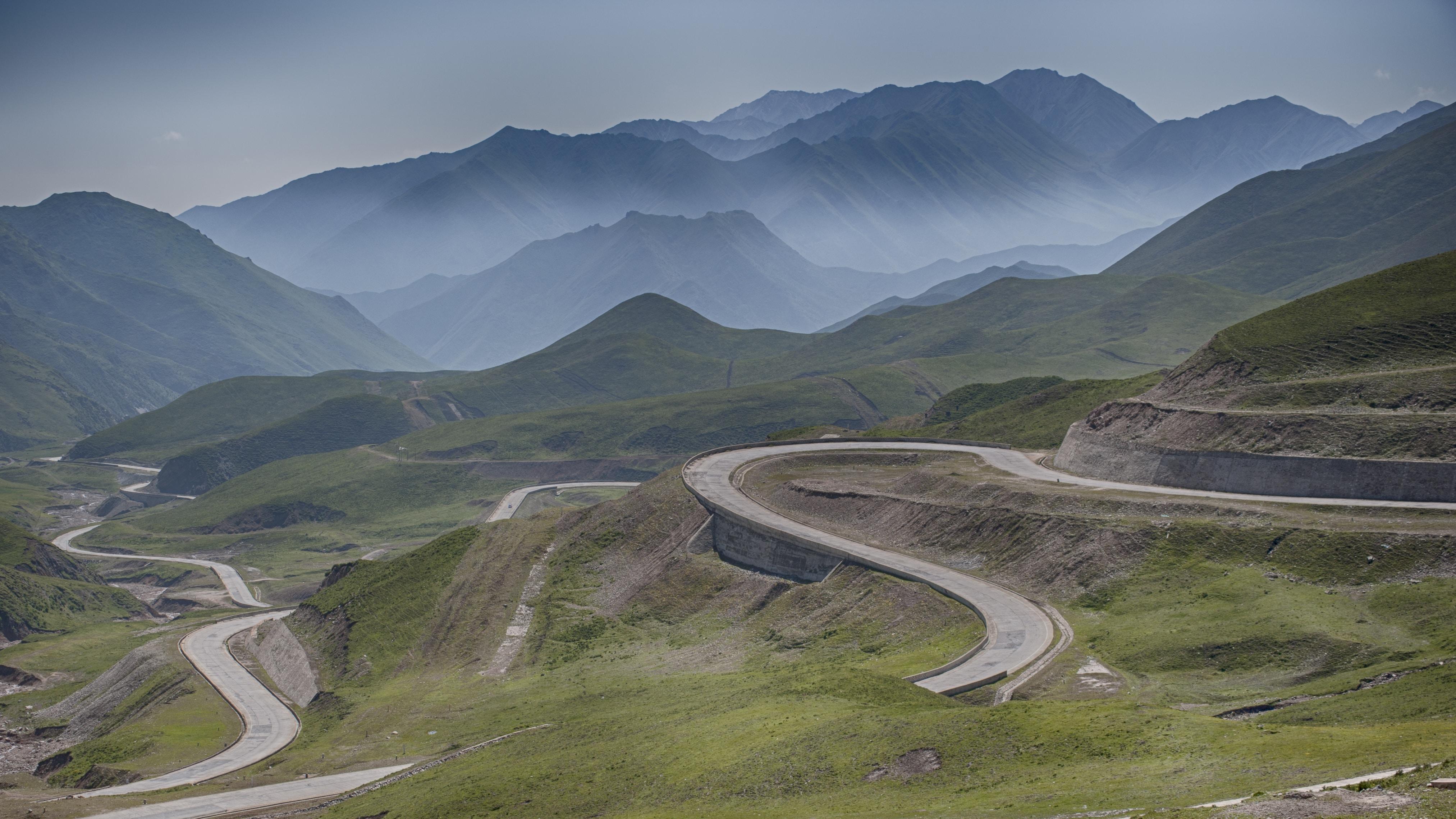 A winding road cutting through green undulating hills