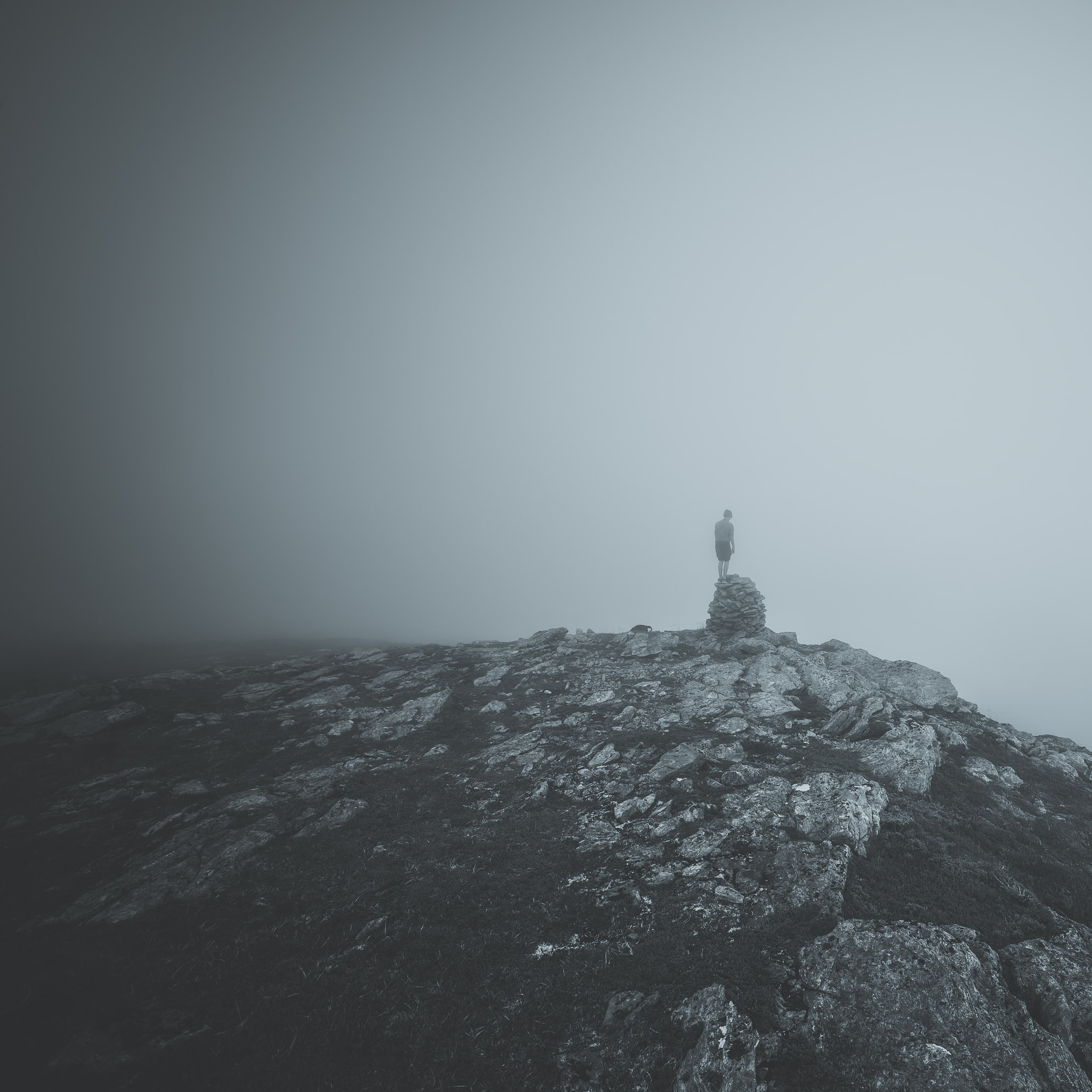 Person stands on a rock formation on a misty rocky mountain