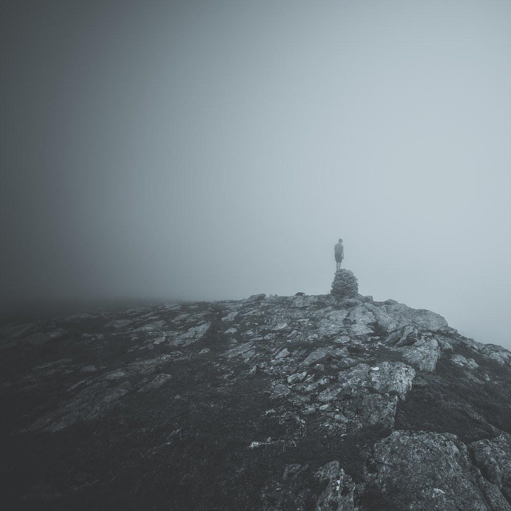 person standing on rock on top of hill
