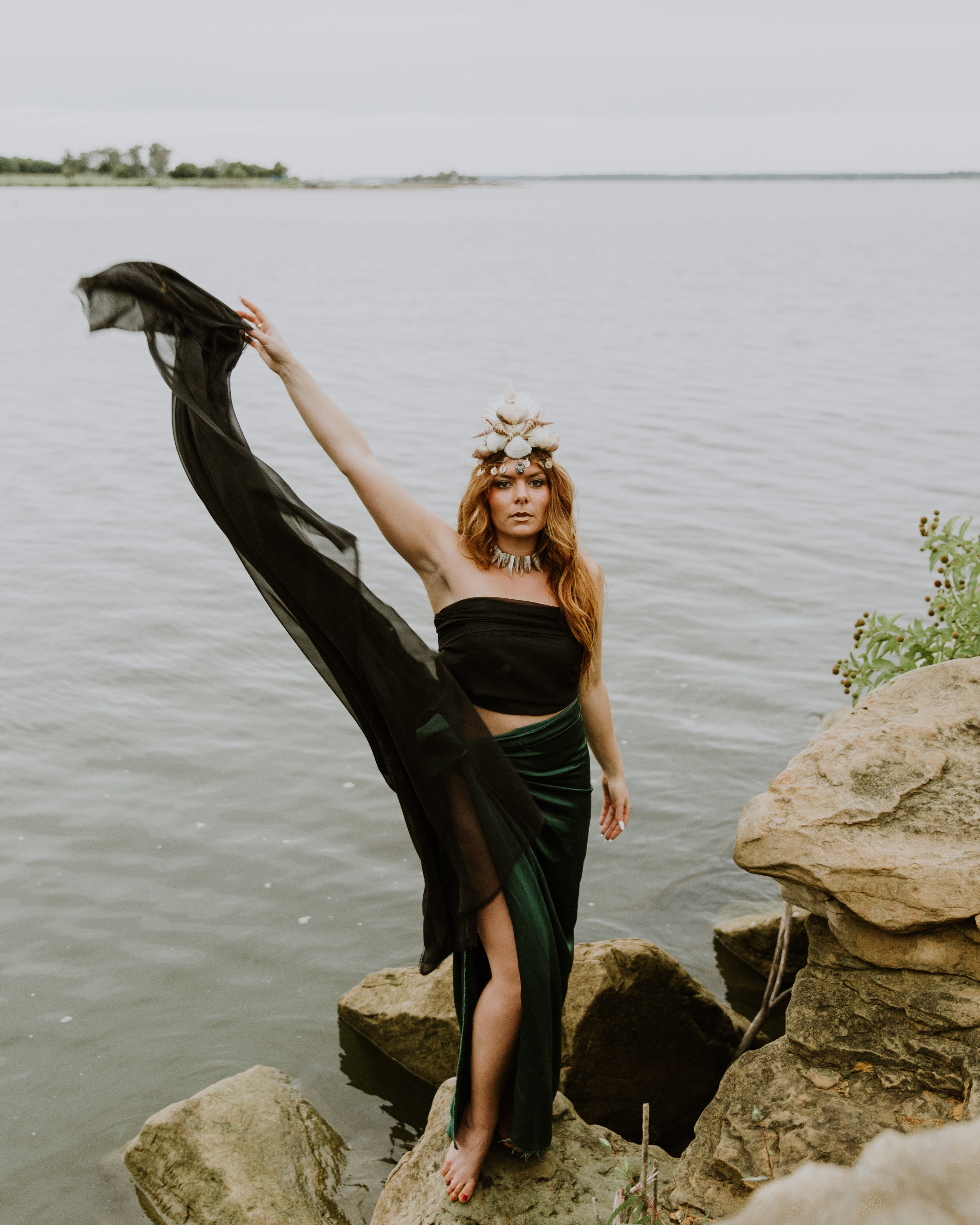 woman waving her dress on stone formation beside body of water