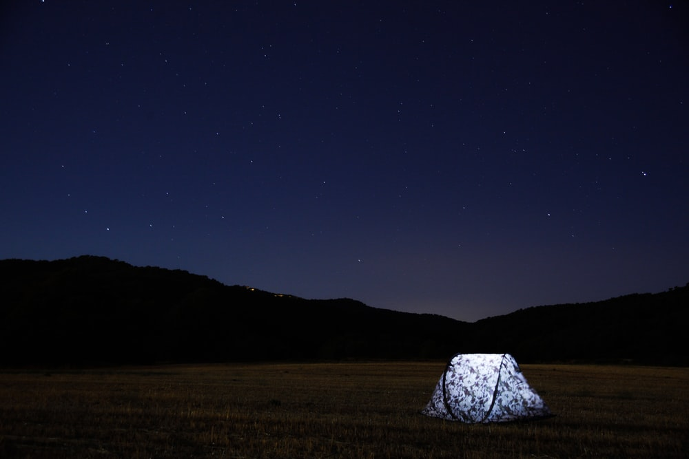 photography of lighted tent on field