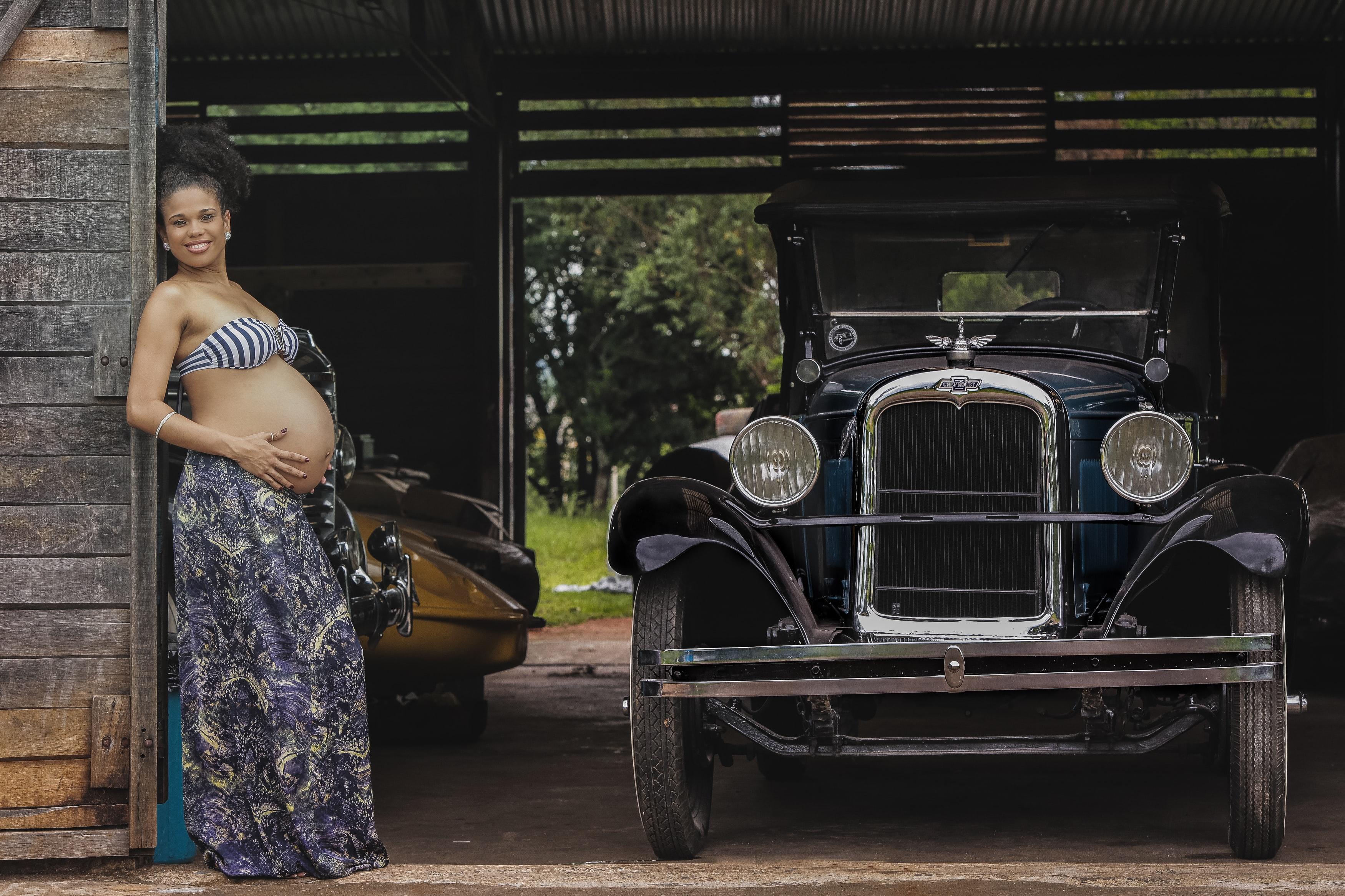 Smiling pregnant woman in Brasilia leaning against a wooden garage wall next to an antique Chevrolet