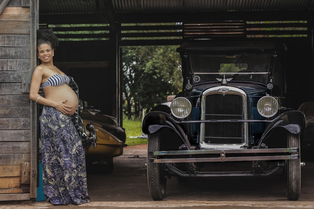pregnant woman near classic car