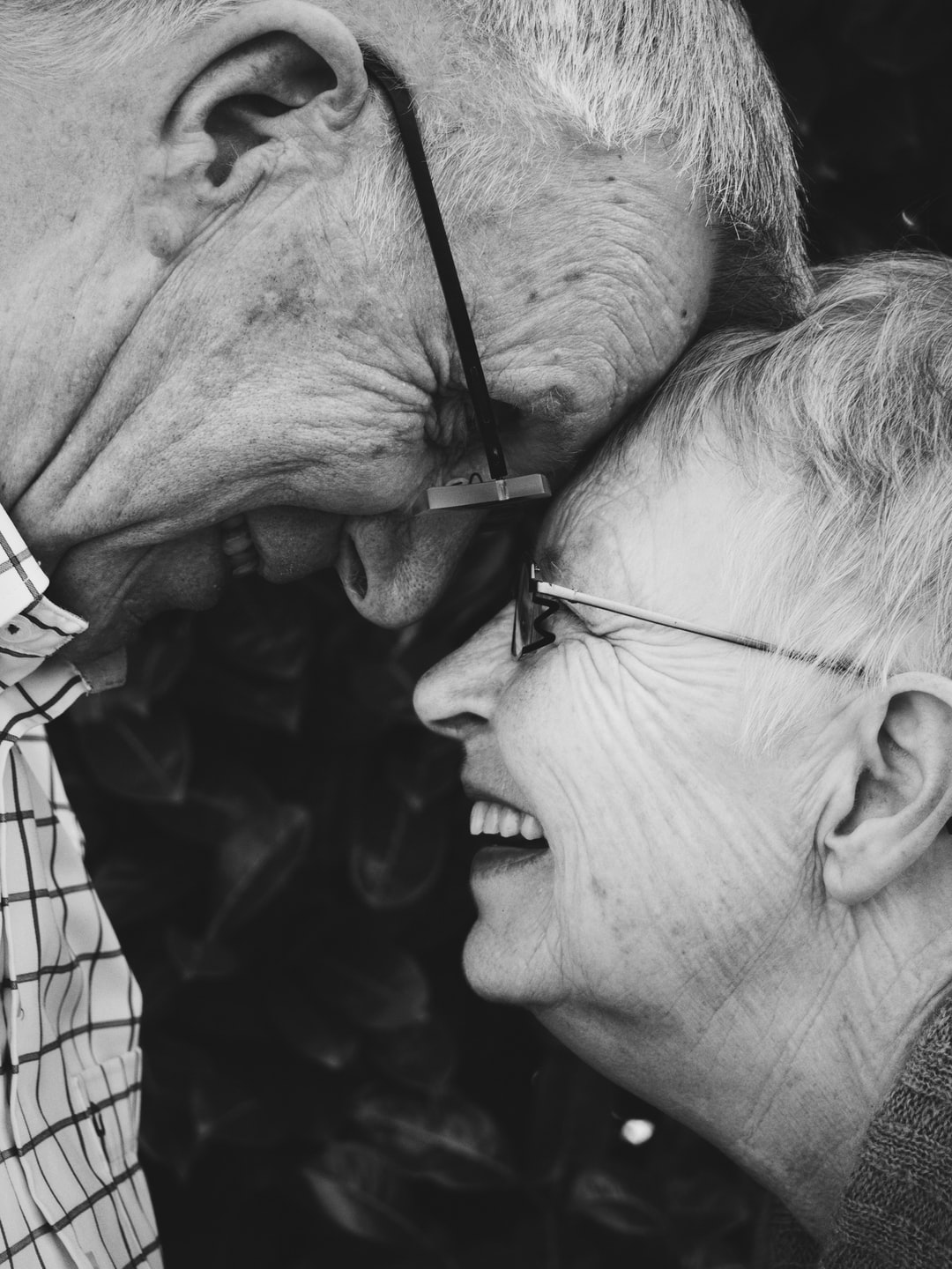 Elderly man and woman touch foreheads in black and white photo