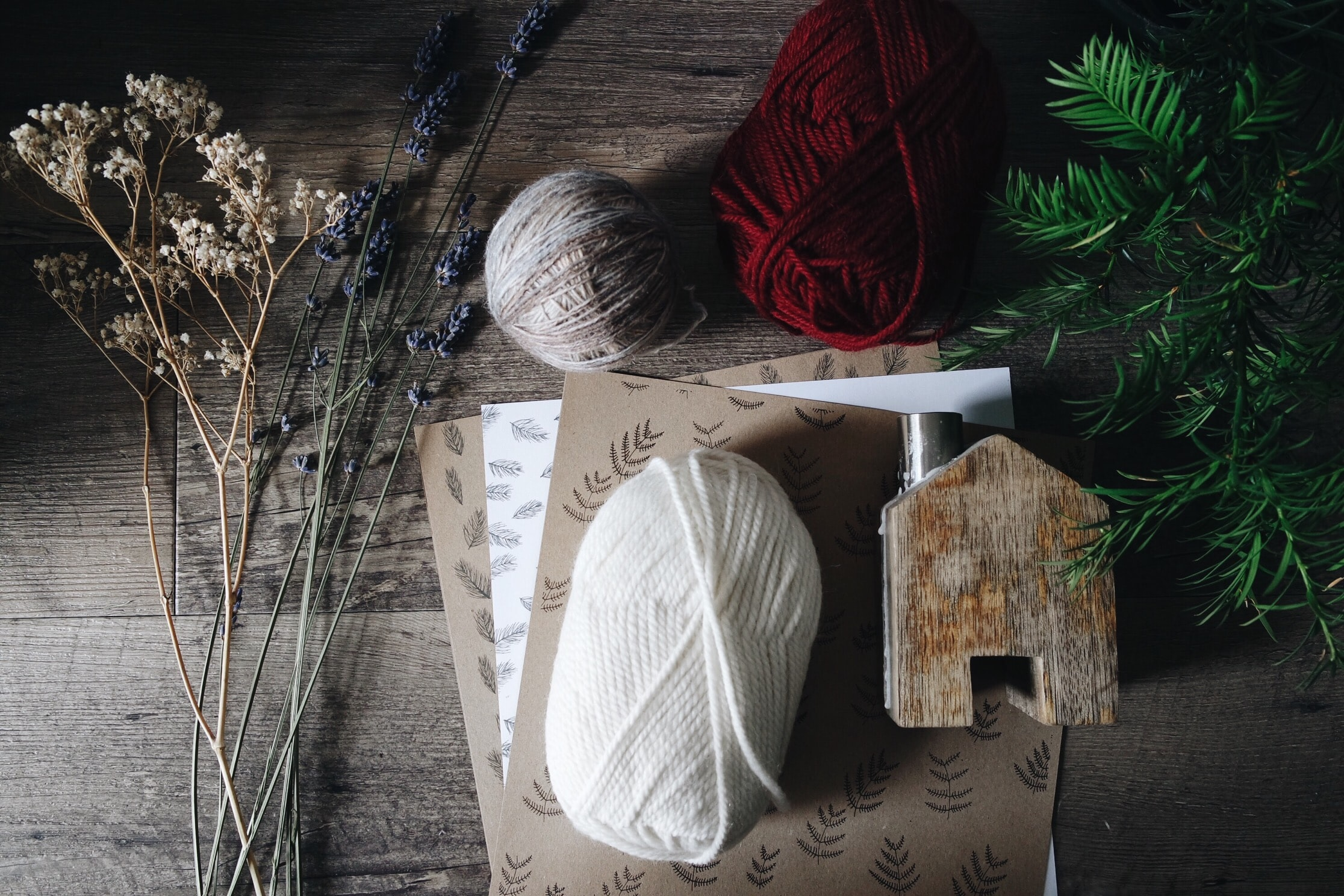 brown, white, and red yarn near flowers