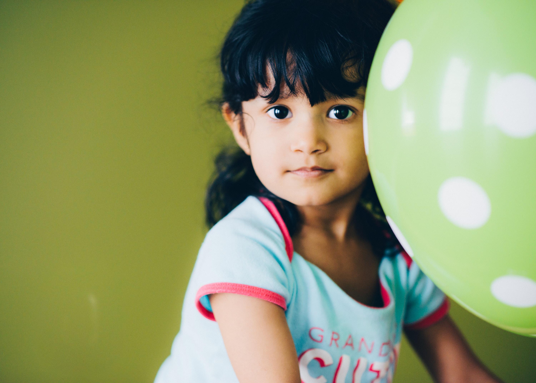girl holding green balloon