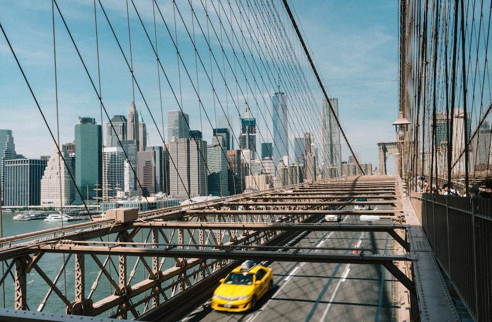 yellow sedan passing on bridge