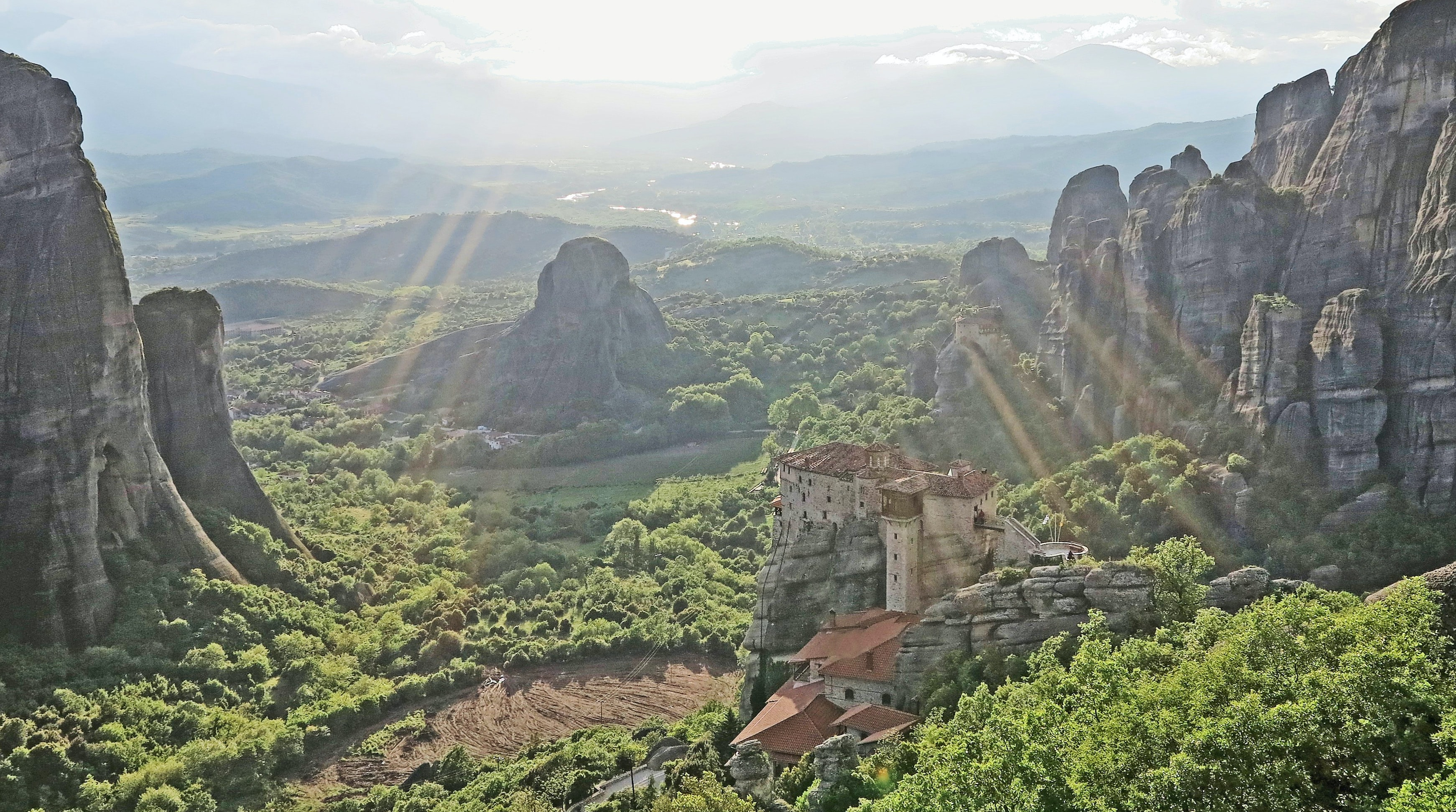 A small castle on the side of a rock formation in Meteora on a bright day