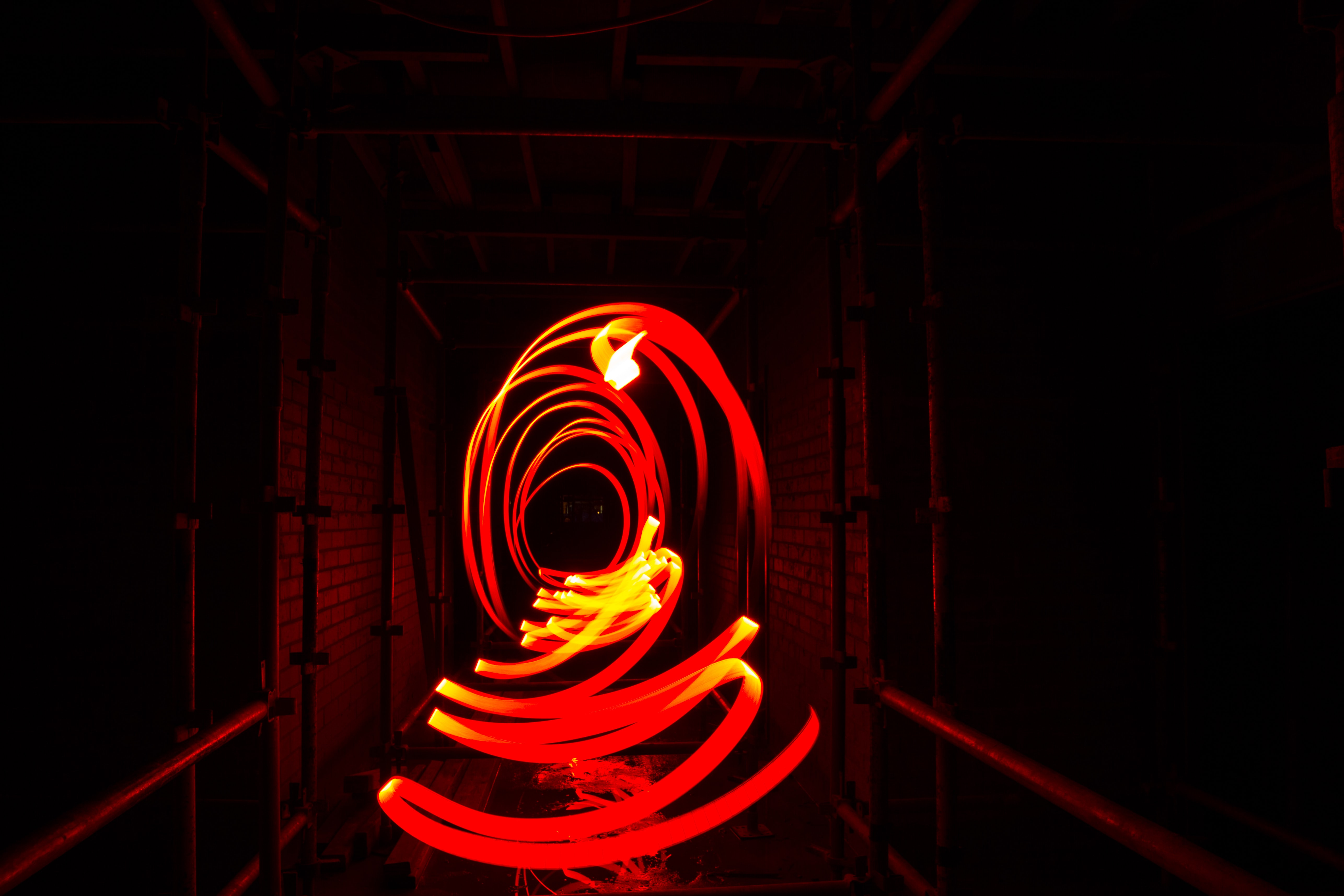 A long exposure shot of circles streaking from a bright red light trail