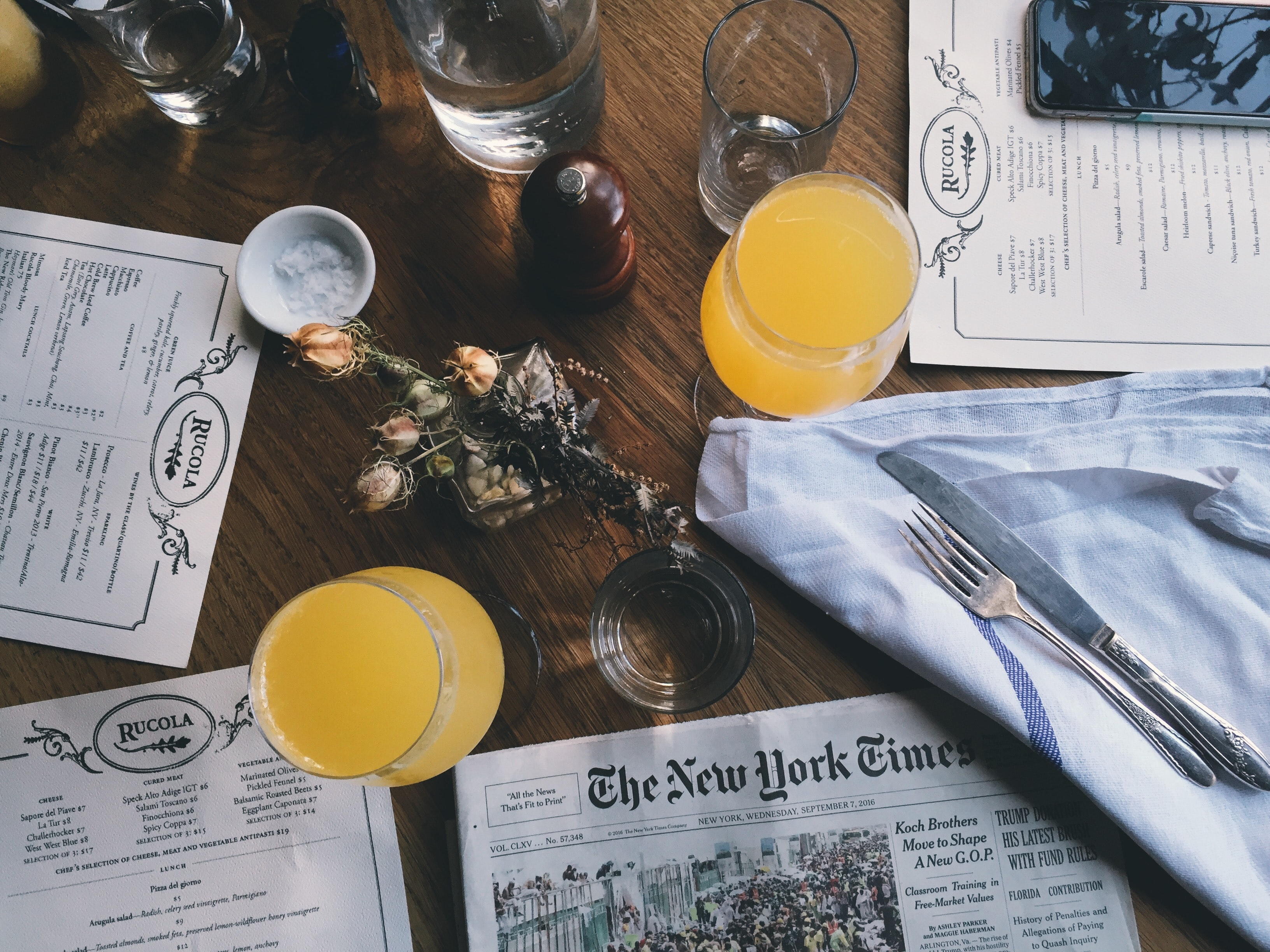 An overhead shot of a restaurant table with glasses of juice and water around a small floral bouquet