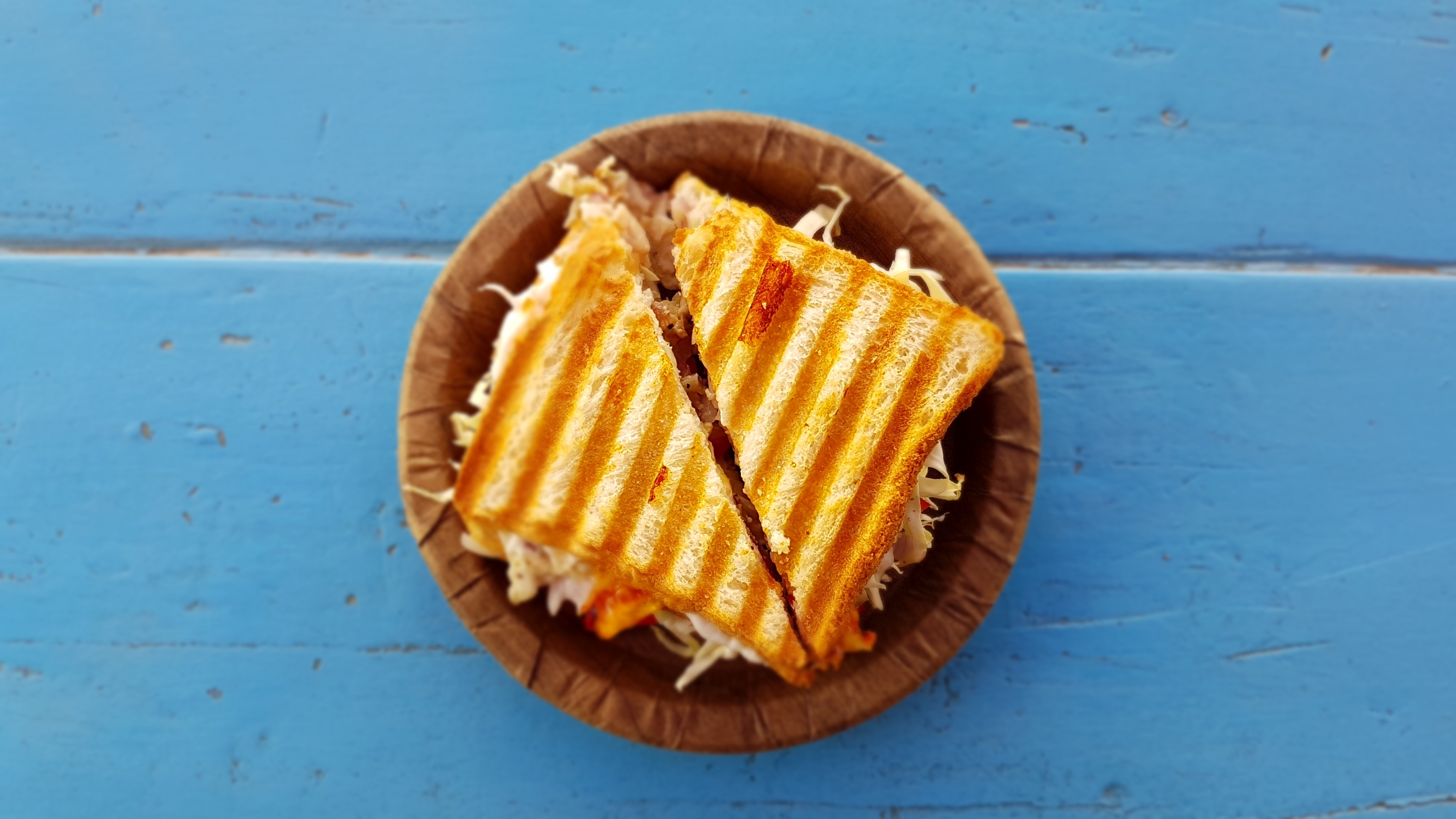 Grilled panini sandwich on a blue background