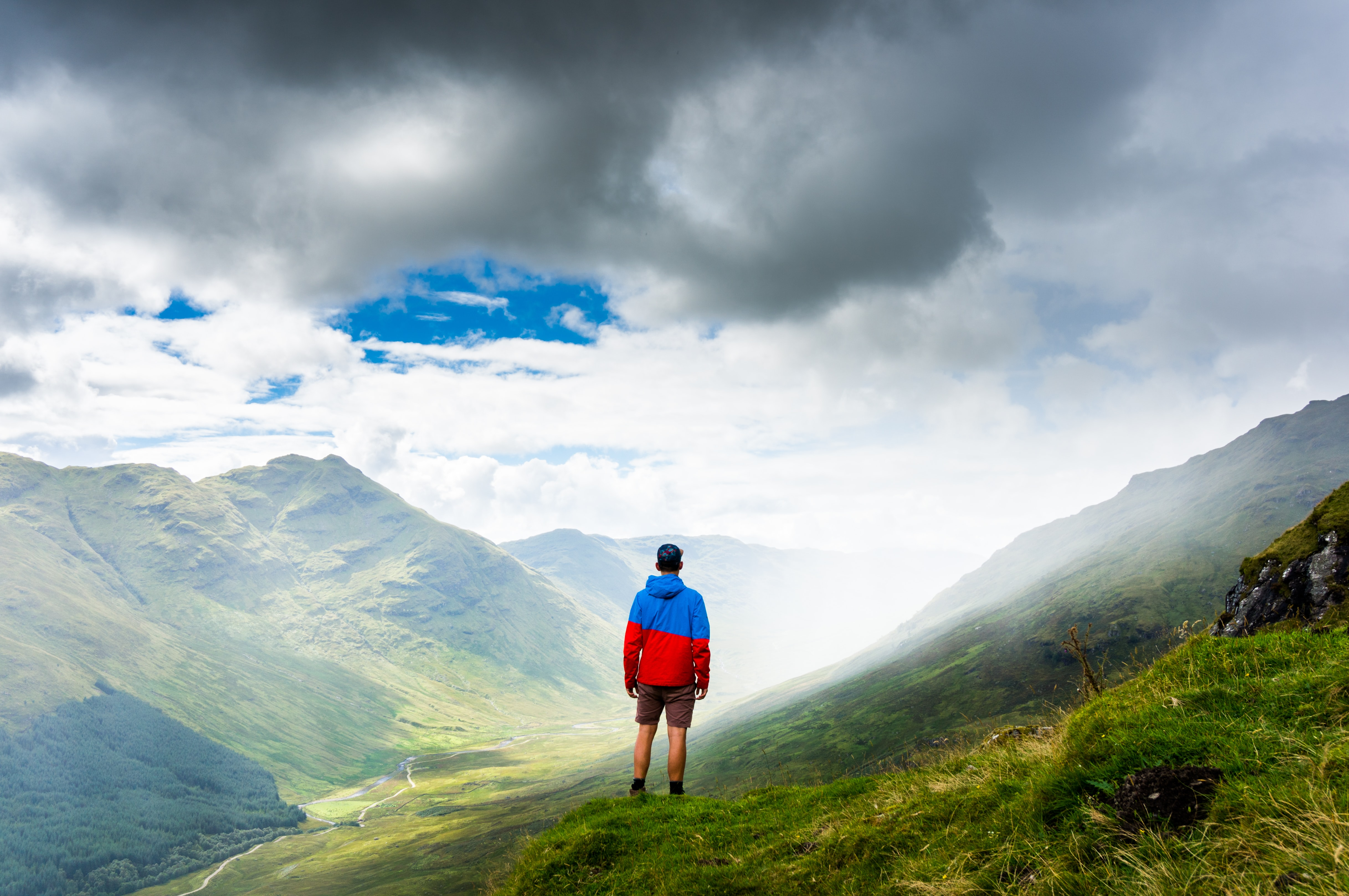 A man wearing a hat, a black and red jacket, and shorts standing on a grassy mountain in Inverlochlarig Farm
